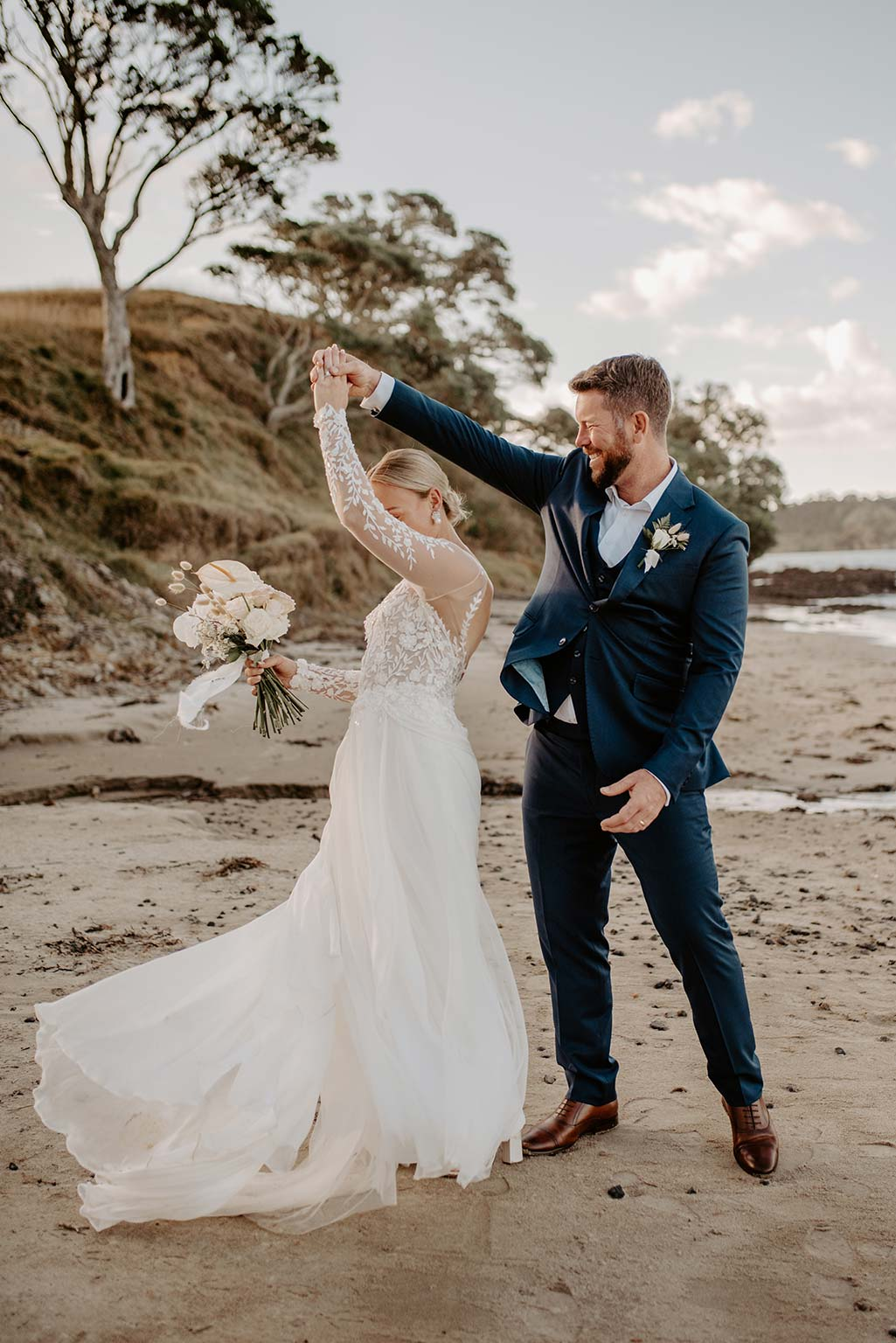 Vinka Design Features Real Weddings - bride and groom dance on the sand - bride wearing a bespoke Makaira gown with silk-chiffon and tulle overskirt giving her a beautiful train which could be removed later on to reveal a floor length party dress