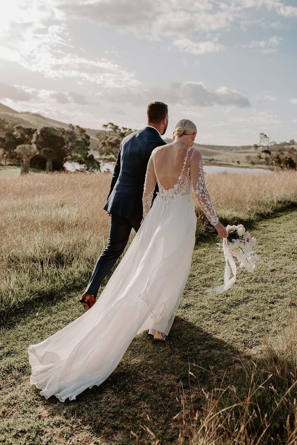 Vinka Design Features Real Weddings - bride and groom walk next to the ocean - bride wearing a bespoke Makaira gown with silk-chiffon and tulle overskirt giving her a beautiful train which could be removed later on to reveal a floor length party dress