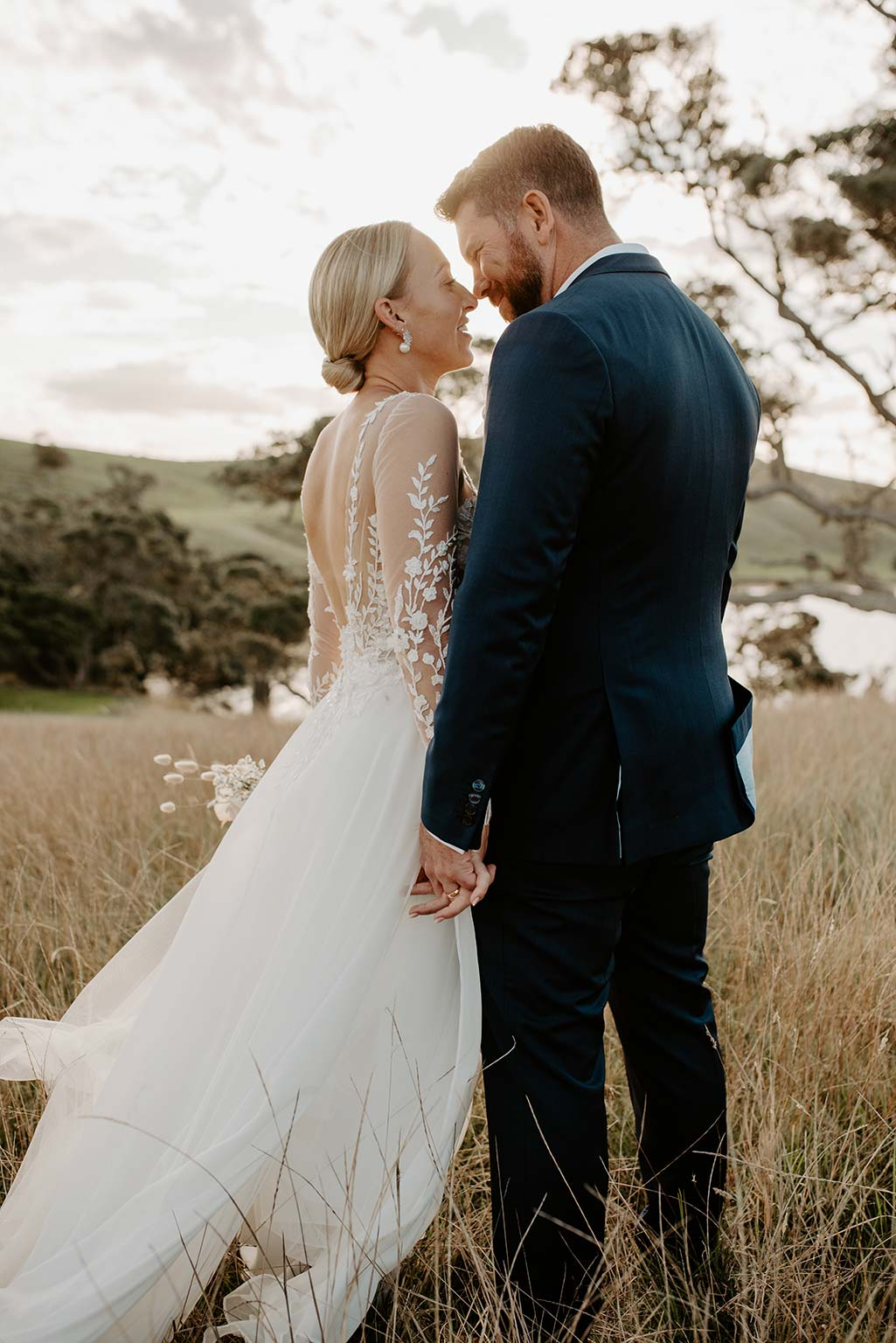 Vinka Design Features Real Weddings - bride and groom embrace - bride wearing a bespoke Makaira gown with silk-chiffon and tulle overskirt giving her a beautiful train which could be removed later on to reveal a floor length party dress
