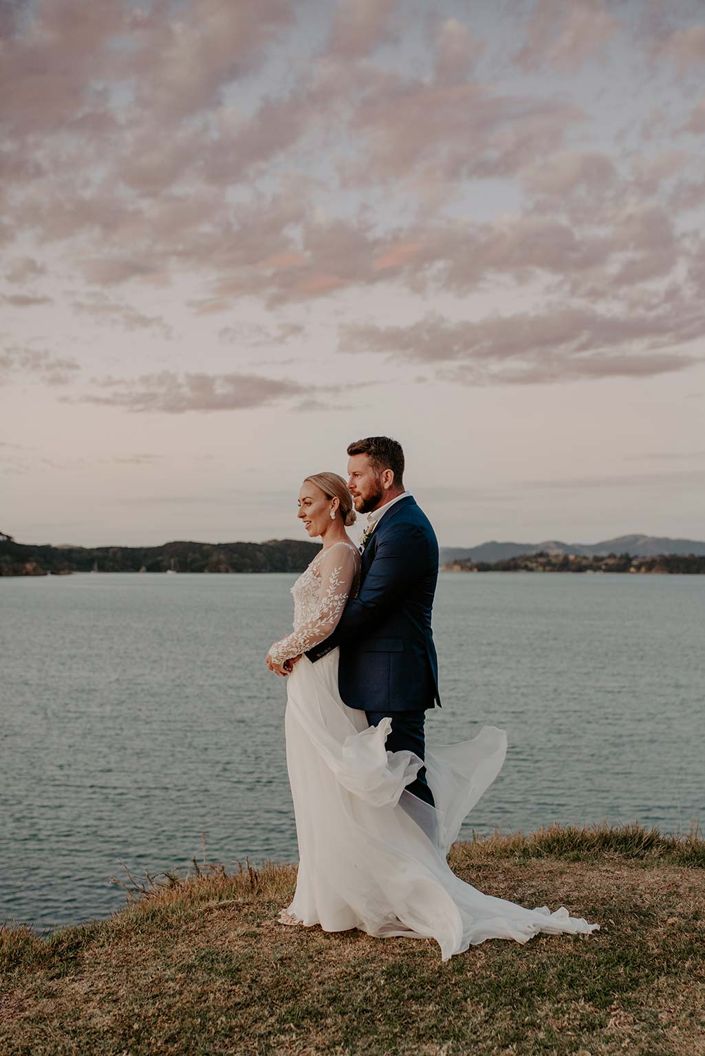Vinka Design Features Real Weddings - bride and groom embrace next to the ocean - bride wearing a bespoke Makaira gown with silk-chiffon and tulle overskirt giving her a beautiful train which could be removed later on to reveal a floor length party dress