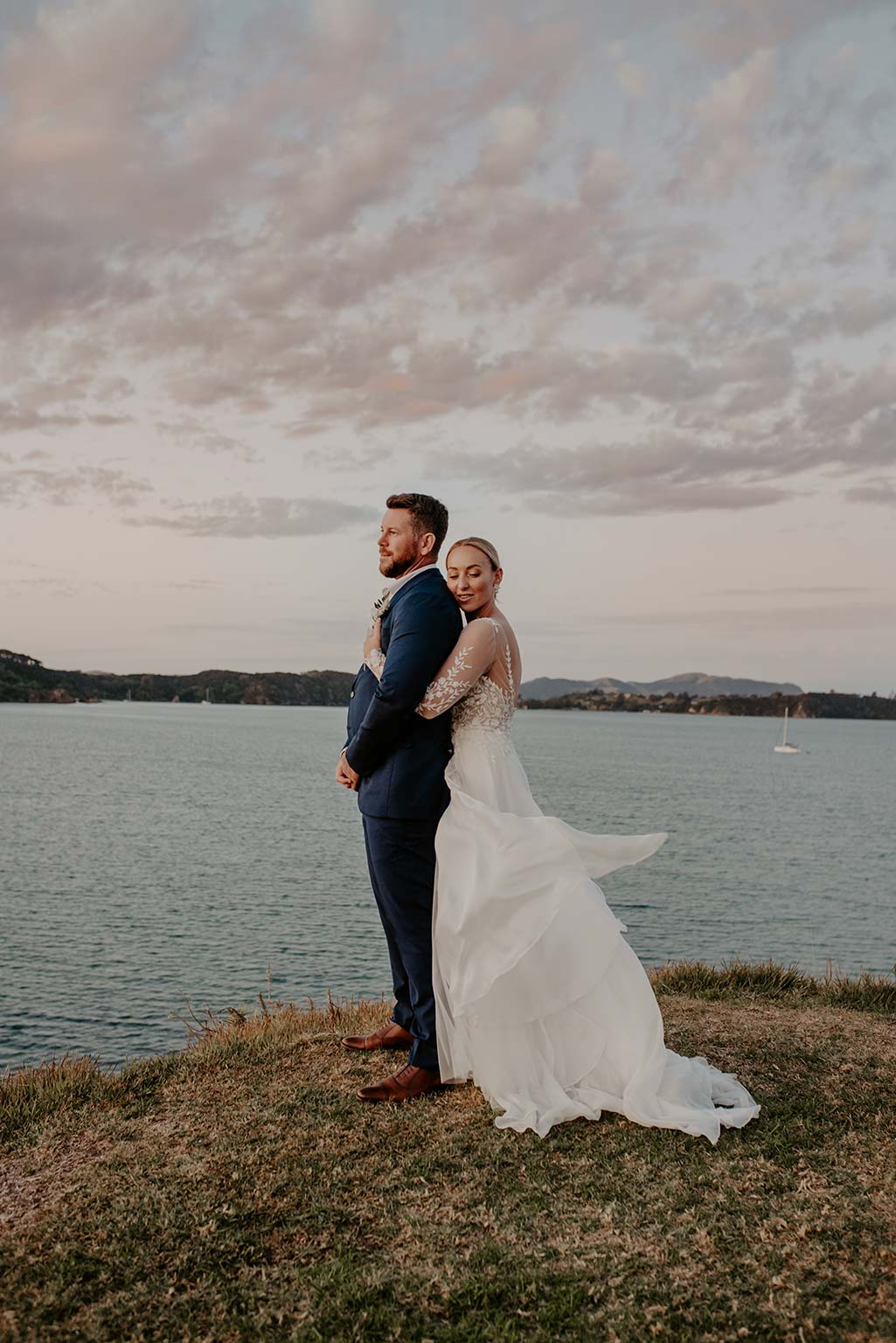 Vinka Design Features Real Weddings - bride embracing groom from the back - wearing a bespoke Makaira gown with silk-chiffon and tulle overskirt giving her a beautiful train which could be removed later on to reveal a floor length party dress - next to the ocean