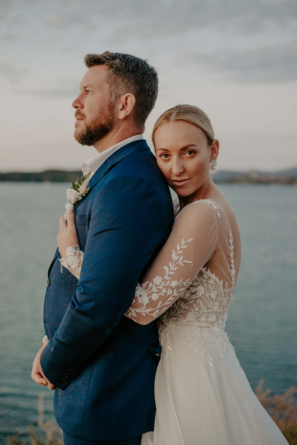 Vinka Design Features Real Weddings - bride embraces groom from the back - wearing a bespoke Makaira gown with silk-chiffon and tulle overskirt giving her a beautiful train which could be removed later on to reveal a floor length party dress