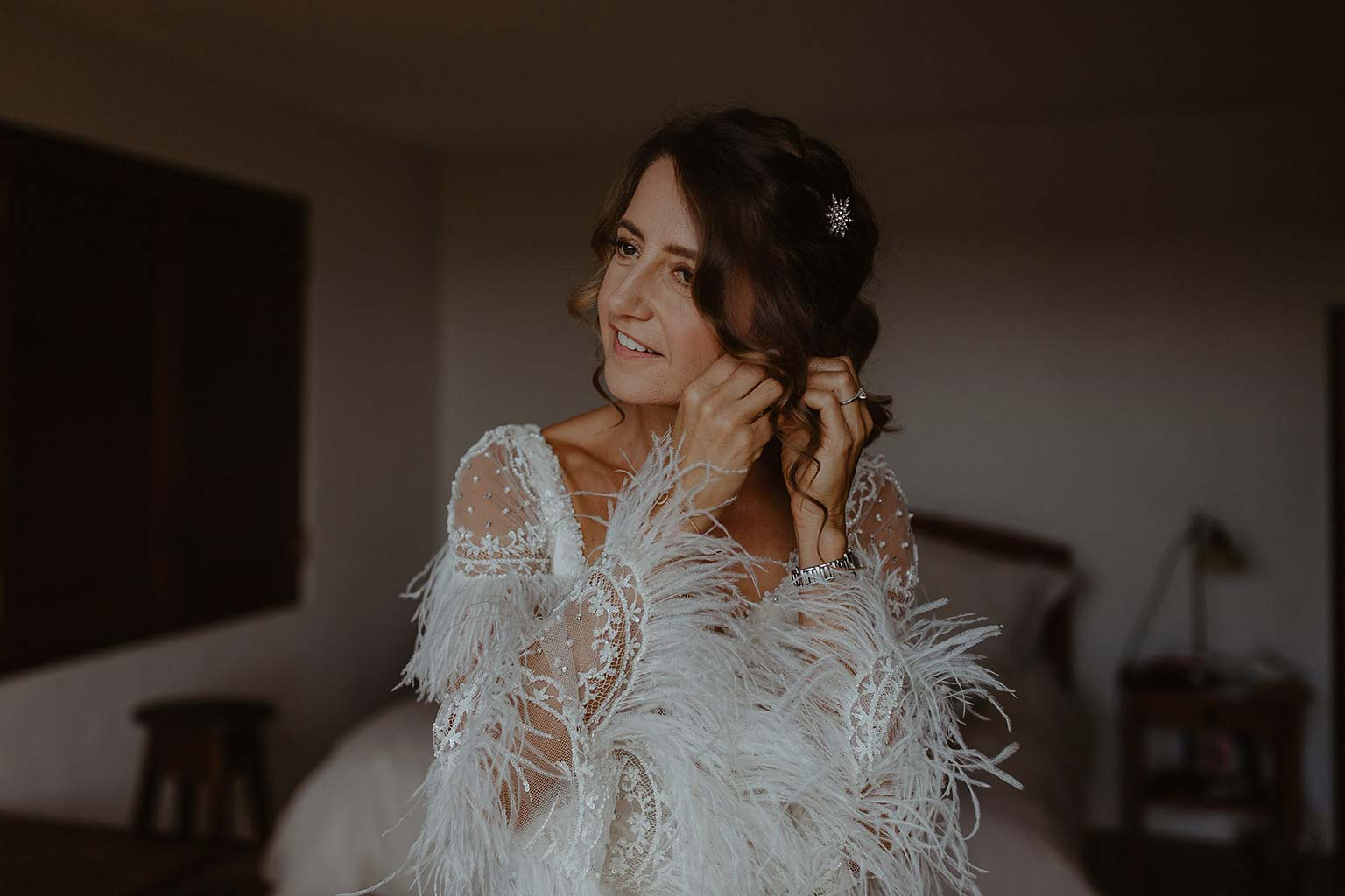 Vinka Design Features Real Weddings - bride getting ready putting on earrings - bride wearing beautiful silk and tulle Chanel wedding dress from the Heart of Havana Collection with added underskirt
