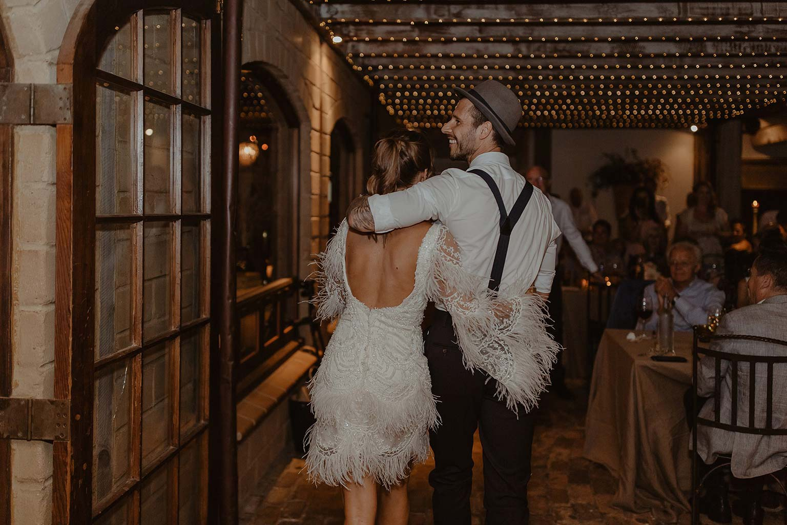 Vinka Design Features Real Weddings - bride and groom arm in arm at wedding reception - bride wearing beautiful silk and tulle Chanel wedding dress from the Heart of Havana Collection