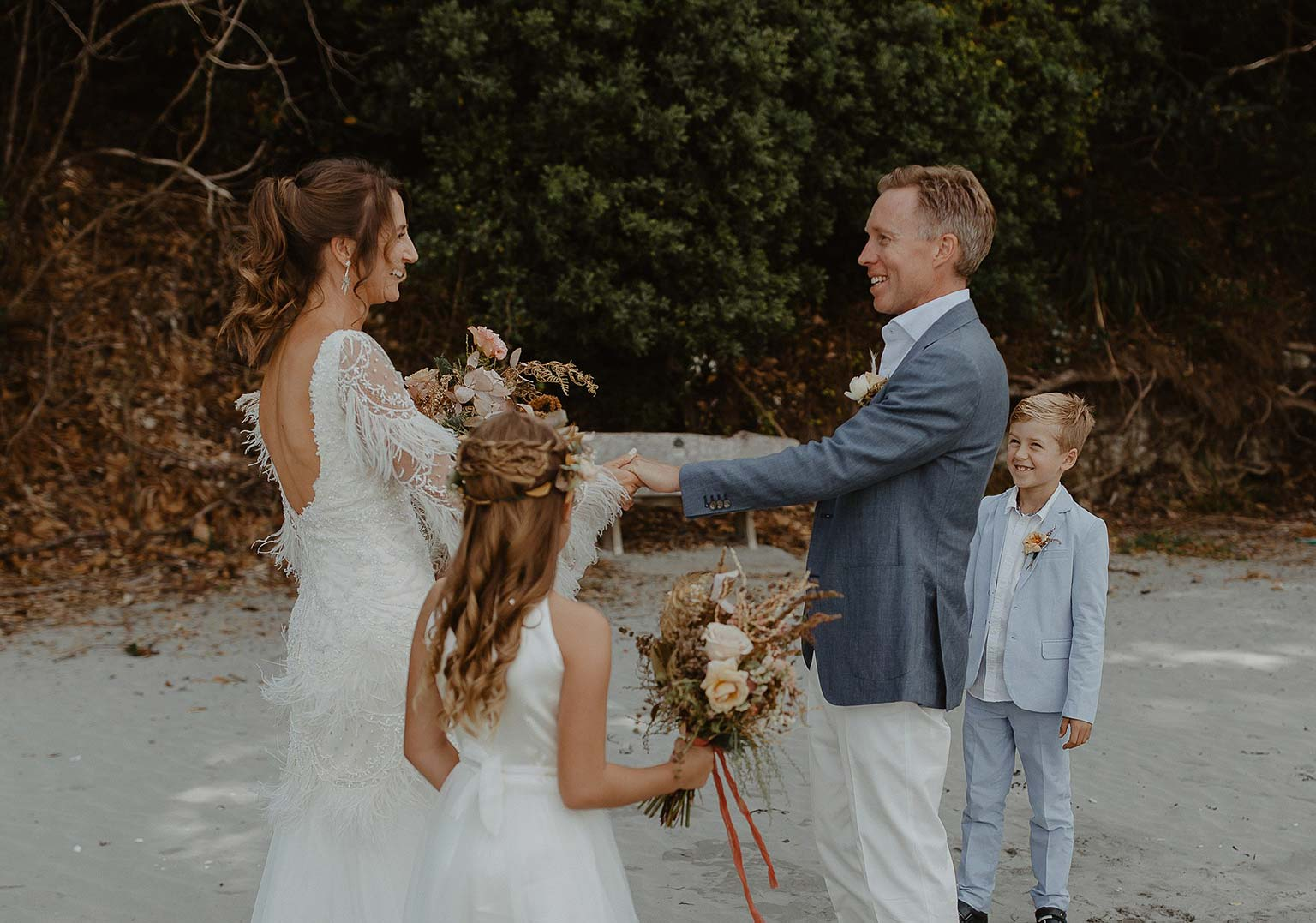 Vinka Design Features Real Weddings - bride with groom and children on the beach - bride wearing beautiful silk and tulle Chanel wedding dress from the Heart of Havana Collection with added underskirt