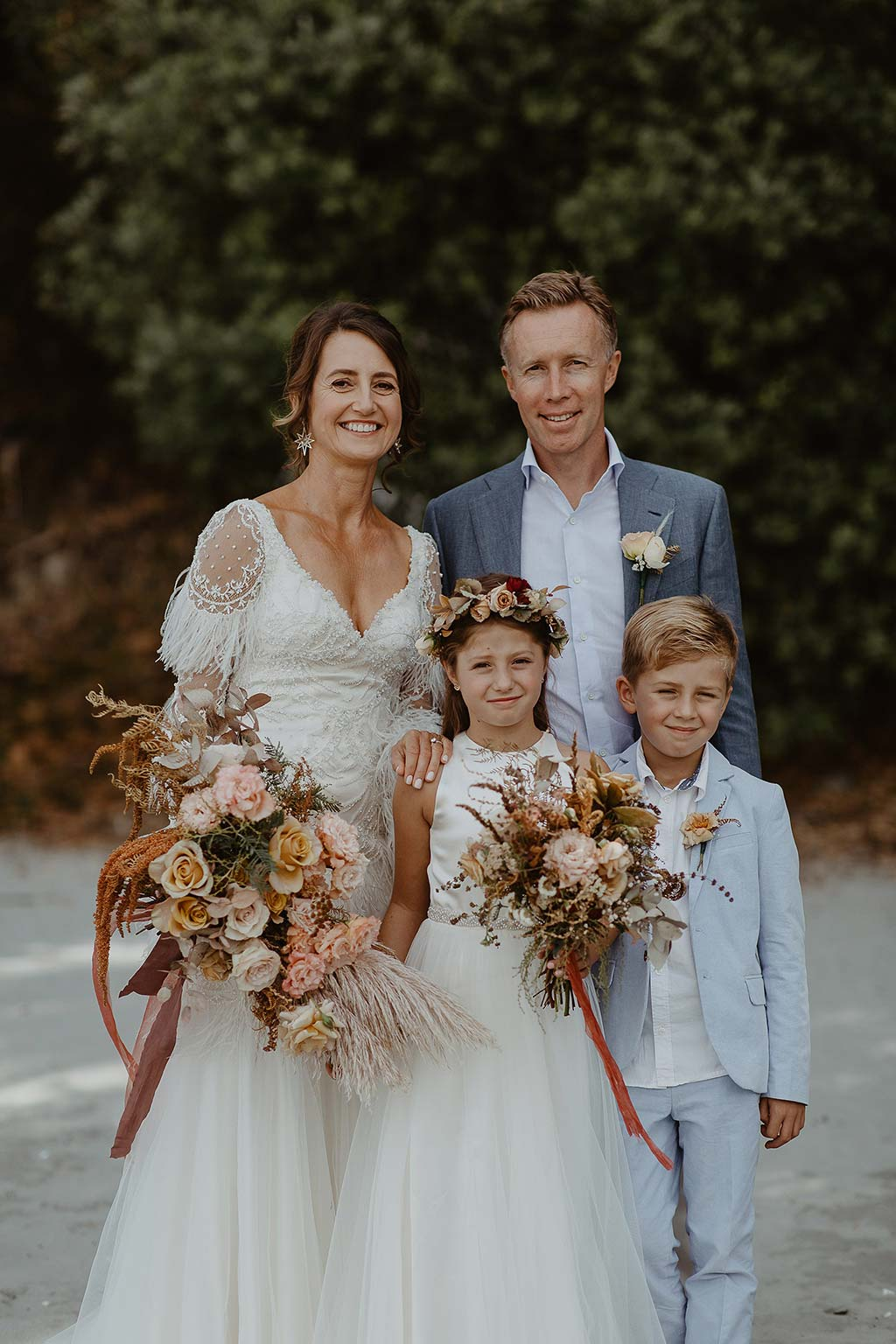 Vinka Design Features Real Weddings - bride wearing beautiful silk and tulle Chanel wedding dress from the Heart of Havana Collection with added underskirt posing with groom, flower girl and page boy on the beach