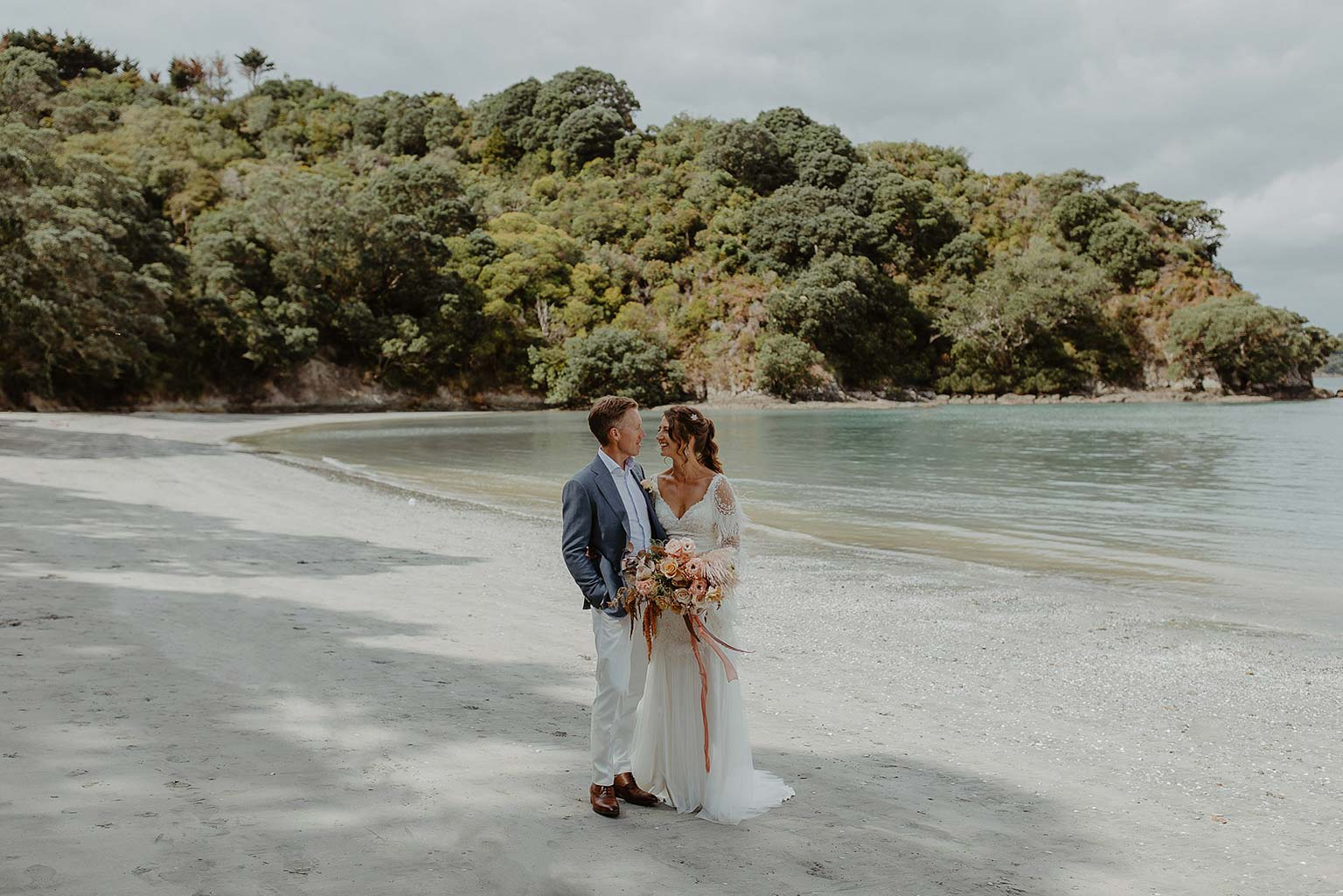 Vinka Design Features Real Weddings - bride wearing beautiful silk and tulle Chanel wedding dress from the Heart of Havana Collection with added underskirt posing on the beach with groom
