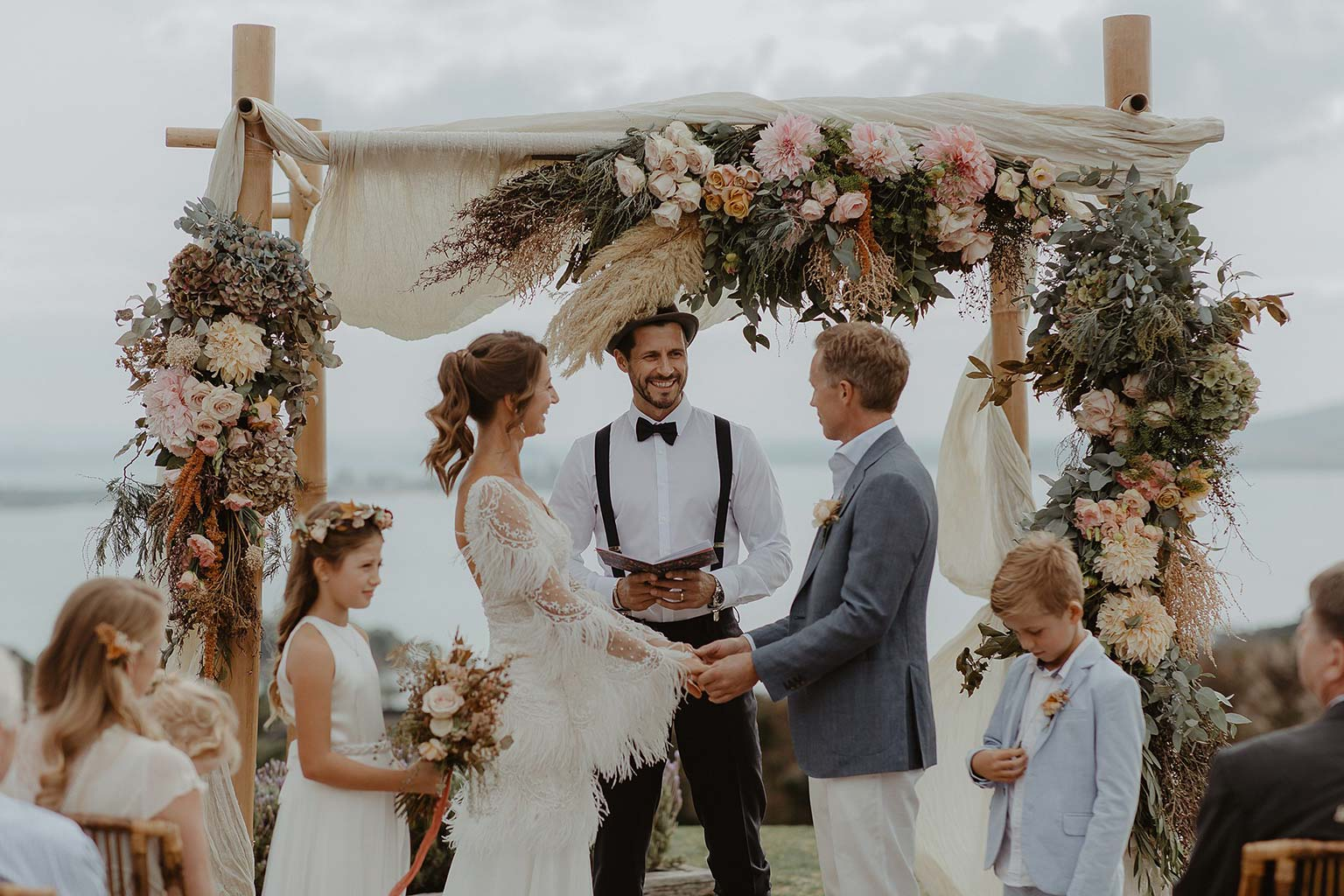 Vinka Design Features Real Weddings - wedding ceremony in front of flower arch - bride wearing beautiful silk and tulle Chanel wedding dress from the Heart of Havana Collection with added underskirt
