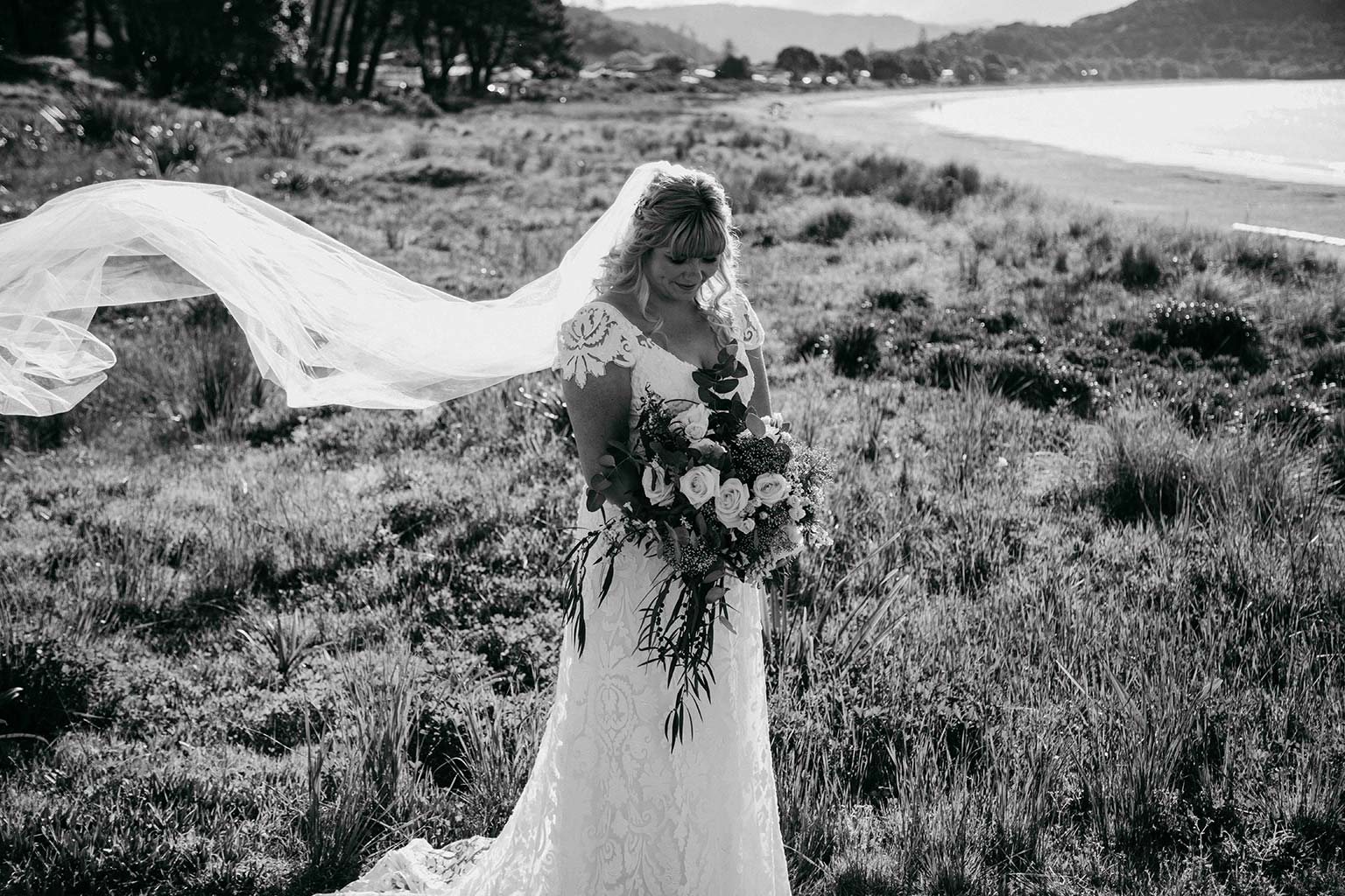Vinka Design Features Real Weddings - bride wearing bespoke Vinka wedding gown - bride poses with bouquet in sand dunes with veil flowing in the wind - in black and white