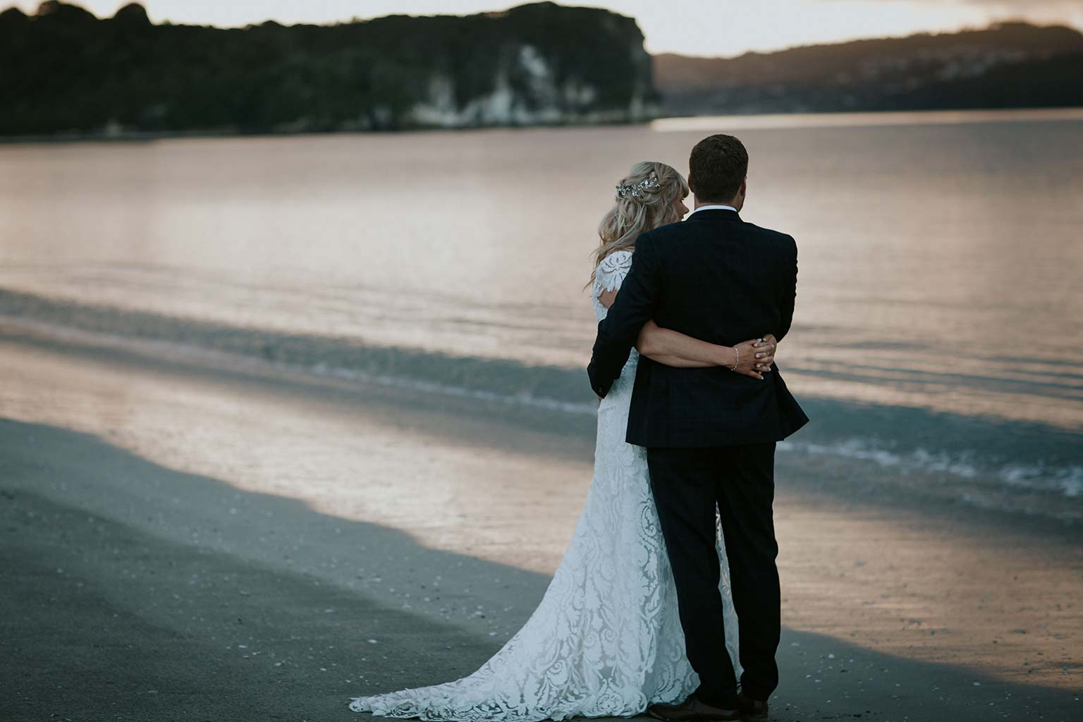 Vinka Design Features Real Weddings - bride wearing bespoke Vinka wedding gown - bride and groom arm in arm next to the ocean on the beach at sunset