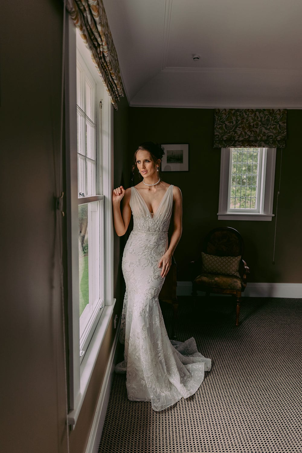 Zana Wedding gown from Vinka Design - Stunning full-lace form-fitting wedding dress. Hand appliqued delicate sequins & beads with platinum embroidery across the front and back of the bodice, Swarovski buttons on the illusion tulle back. Model wearing gown inside boutique room.