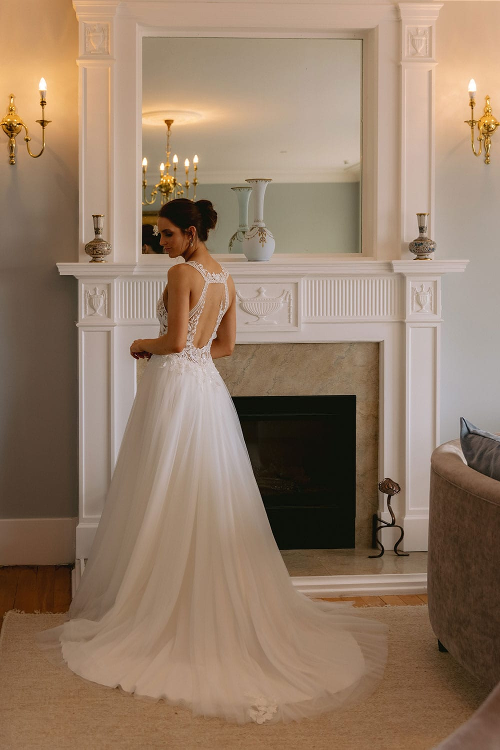 Tia Wedding gown from Vinka Design - This dreamy sculpted wedding dress has a deep V-shaped illusion neckline with beaded floral lace and an open back. The skirt has layers of soft tulle that glide with movement. Model wearing gown showing full length inside warmly lit heritage room.