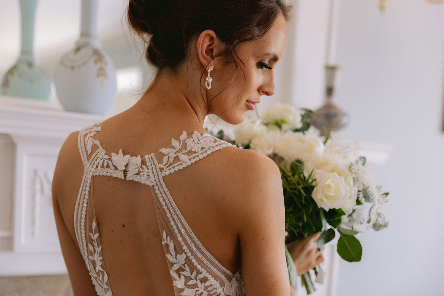 Tia Wedding gown from Vinka Design - This dreamy sculpted wedding dress has a deep V-shaped illusion neckline with beaded floral lace and an open back. The skirt has layers of soft tulle that glide with movement. Model wearing gown showing beautiful open back lace detail, inside warmly lit heritage room.