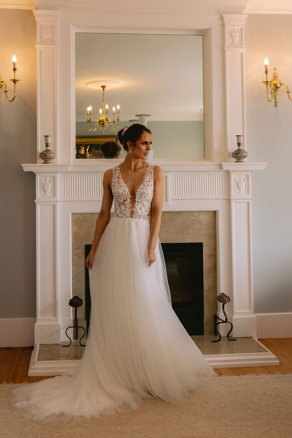 Tia Wedding gown from Vinka Design - This dreamy sculpted wedding dress has a deep V-shaped illusion neckline with beaded floral lace and an open back. The skirt has layers of soft tulle that glide with movement. Model wearing gown showing full length with train to the side, inside warmly lit heritage room.
