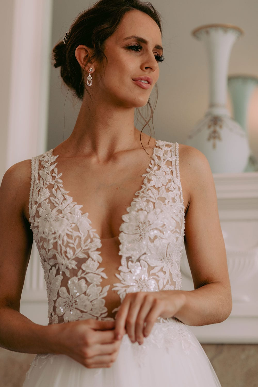 Tia Wedding gown from Vinka Design - This dreamy sculpted wedding dress has a deep V-shaped illusion neckline with beaded floral lace and an open back. The skirt has layers of soft tulle that glide with movement. Model wearing gown showing lace detail of dress bodice and straps, and V-neckline, inside warmly lit heritage room.