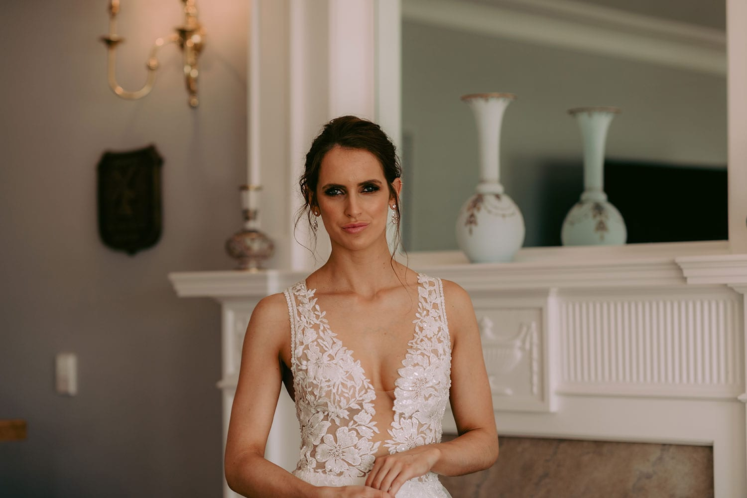 Tia Wedding gown from Vinka Design - This dreamy sculpted wedding dress has a deep V-shaped illusion neckline with beaded floral lace and an open back. The skirt has layers of soft tulle that glide with movement. Model wearing gown showing lace detail of bodice and straps, and V-neckline, inside warmly lit heritage room.