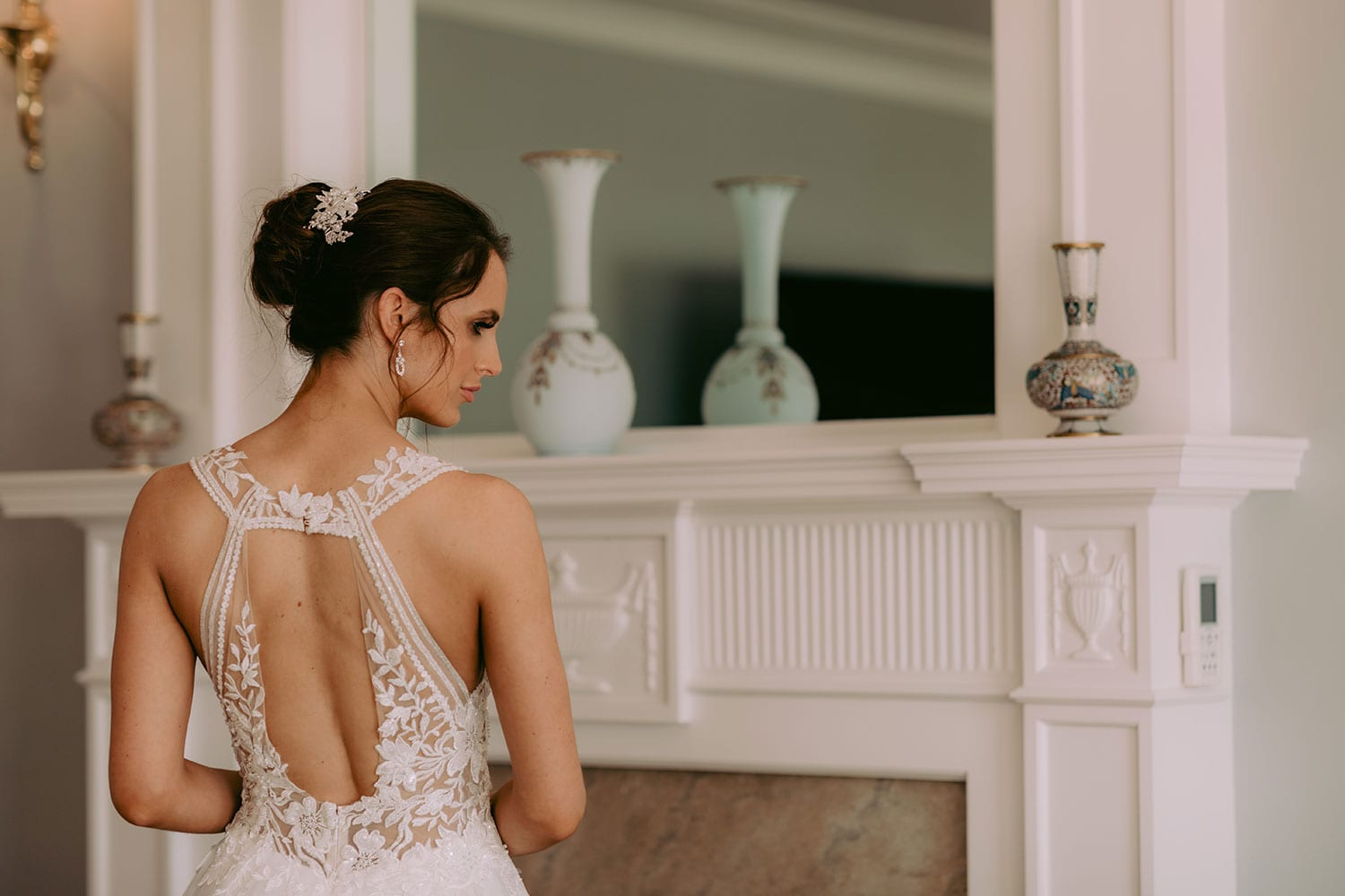 Tia Wedding gown from Vinka Design - This dreamy sculpted wedding dress has a deep V-shaped illusion neckline with beaded floral lace and an open back. The skirt has layers of soft tulle that glide with movement. Model wearing gown showing lace detail open back of dress, inside warmly lit heritage room.