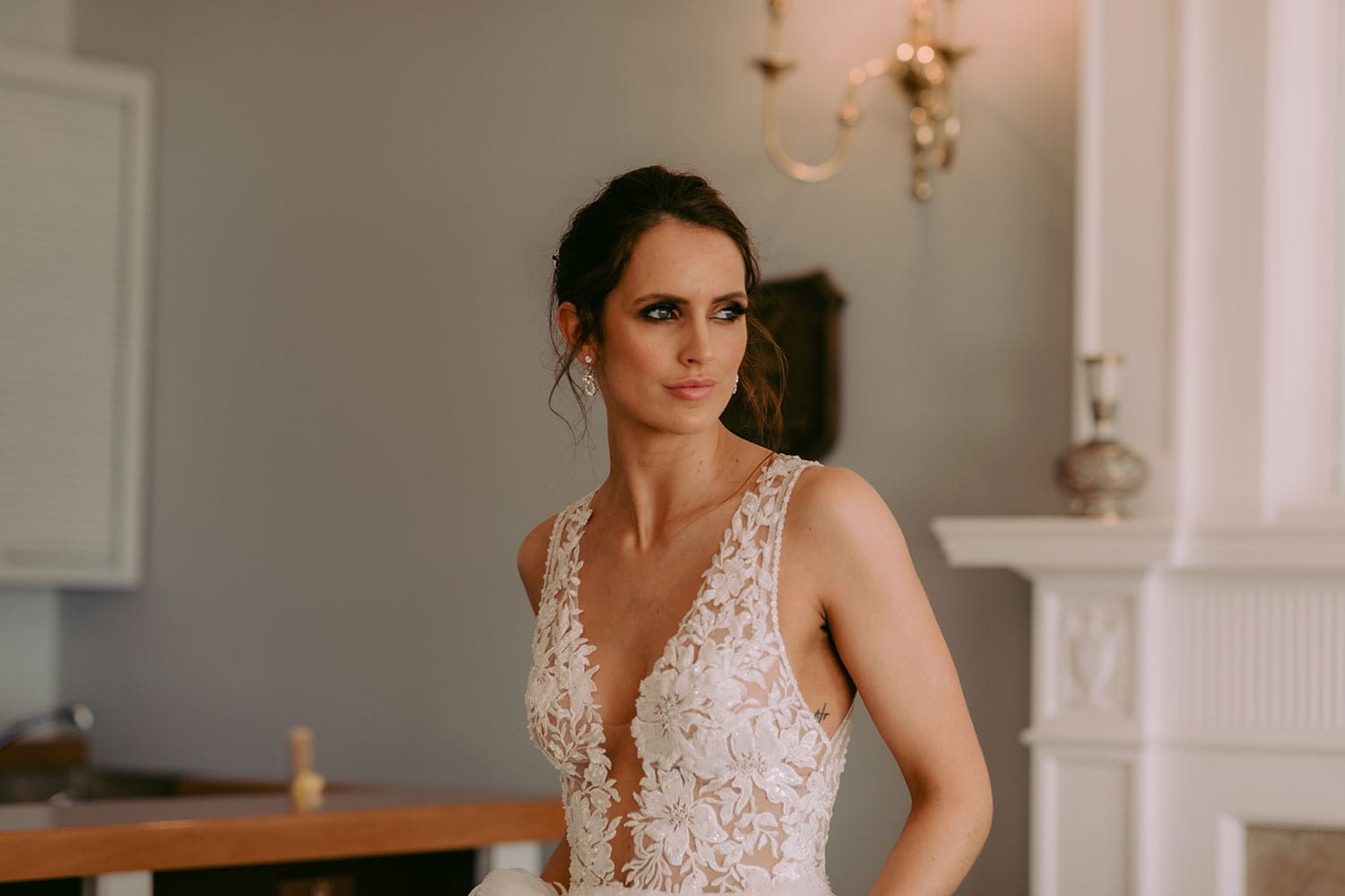 Tia Wedding gown from Vinka Design - This dreamy sculpted wedding dress has a deep V-shaped illusion neckline with beaded floral lace and an open back. The skirt has layers of soft tulle that glide with movement. Model wearing gown showing lace detail of bodice, straps, and V-neckline, inside warmly lit heritage room.