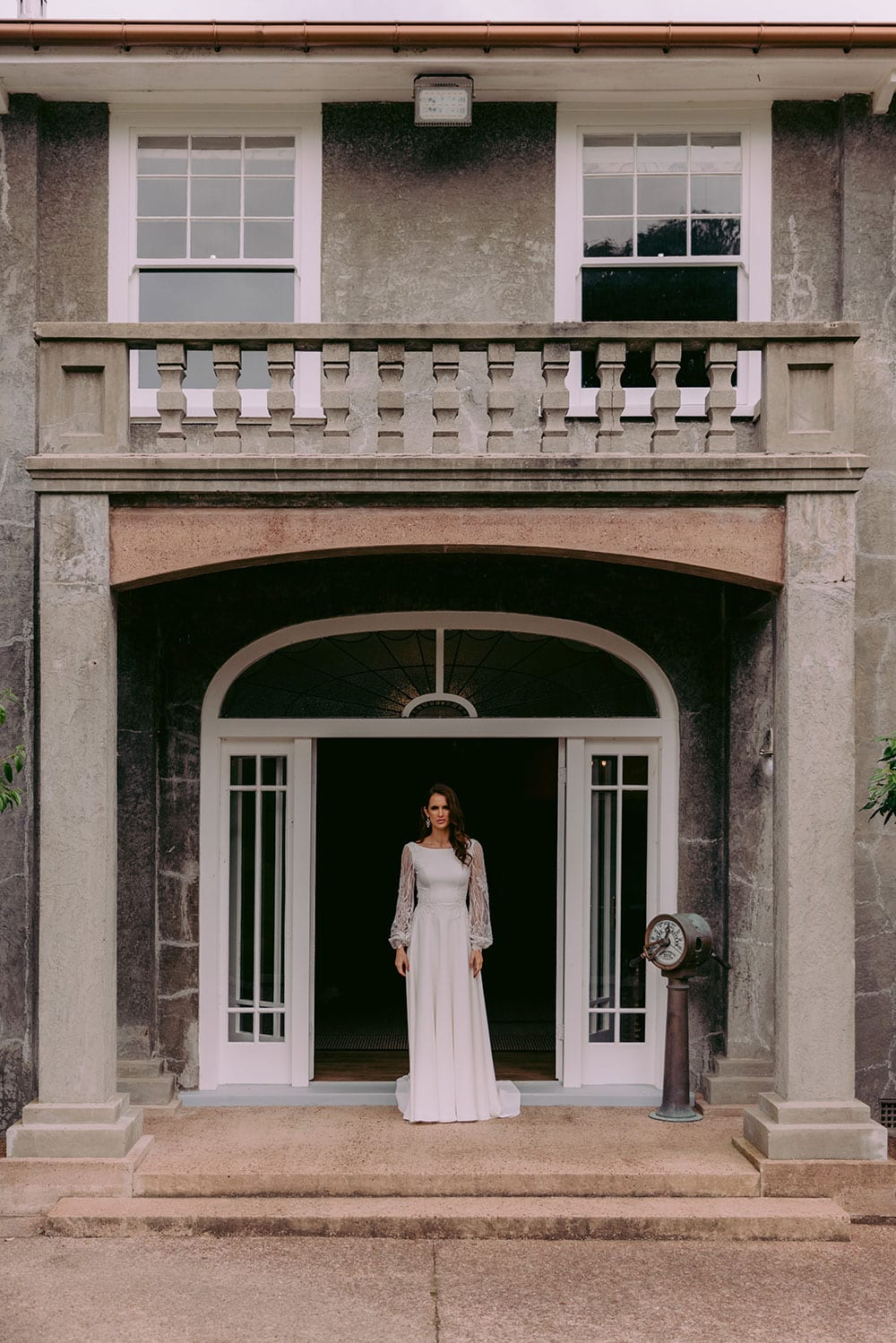 Shiloh Wedding gown from Vinka Design - Beautiful wedding dress with fitted bodice and demure boat neckline, complemented with an open back. Sheer lace sleeves tapered at the wrist with tiny pearl buttons. Lace appliqued waist and train. Model wearing gown in entrance of old heritage building.