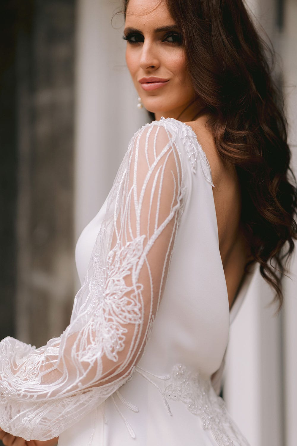 Shiloh Wedding gown from Vinka Design - Beautiful wedding dress with fitted bodice and demure boat neckline, complemented with an open back. Sheer lace sleeves tapered at the wrist with tiny pearl buttons. Lace appliqued waist and train. Model wearing gown showing open dress sleeve lace detail