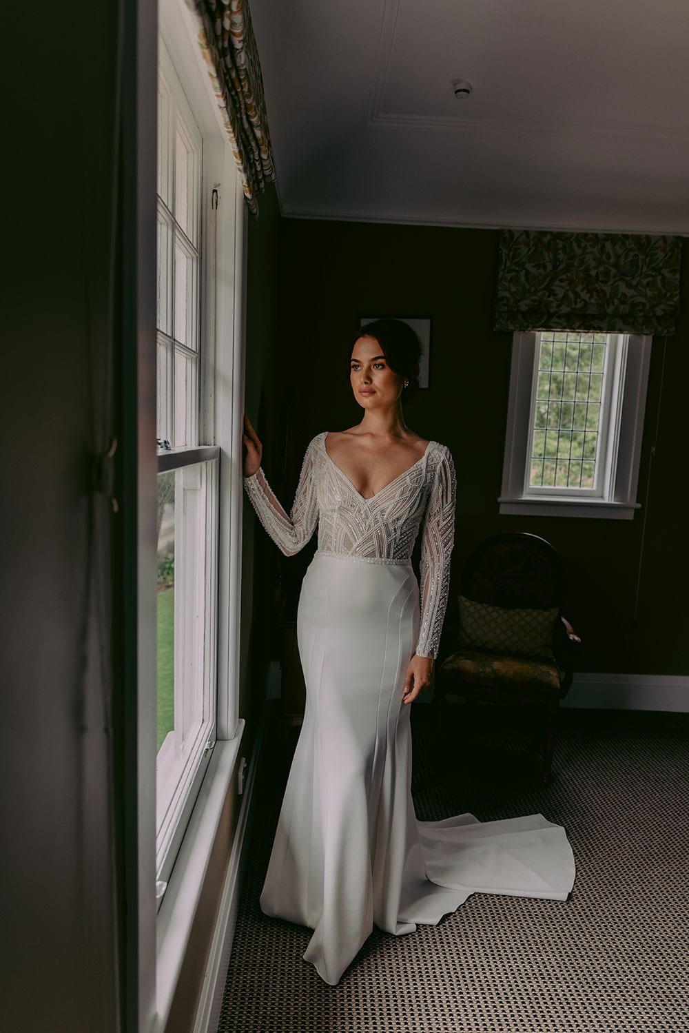 Renata Wedding gown from Vinka Design - Show stopping wedding dress with stunning beaded lace. Fitted sleeves with tiny pearl buttons and open back. Flattering lined panel skirt gently shapes the hips and sculpts into a beautiful flared train. Model wearing gown looking out of window, train flowing behind.