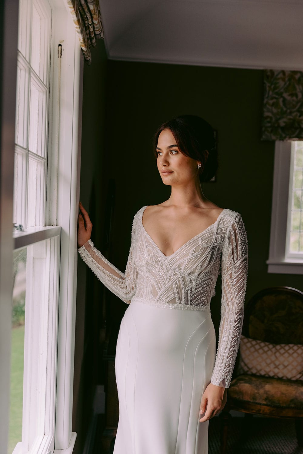Renata Wedding gown from Vinka Design - Show stopping wedding dress with stunning beaded lace. Fitted sleeves with tiny pearl buttons and open back. Flattering lined panel skirt gently shapes the hips and sculpts into a beautiful flared train. Model wearing gown looking out of window, showing close up detail of lace detail of top.