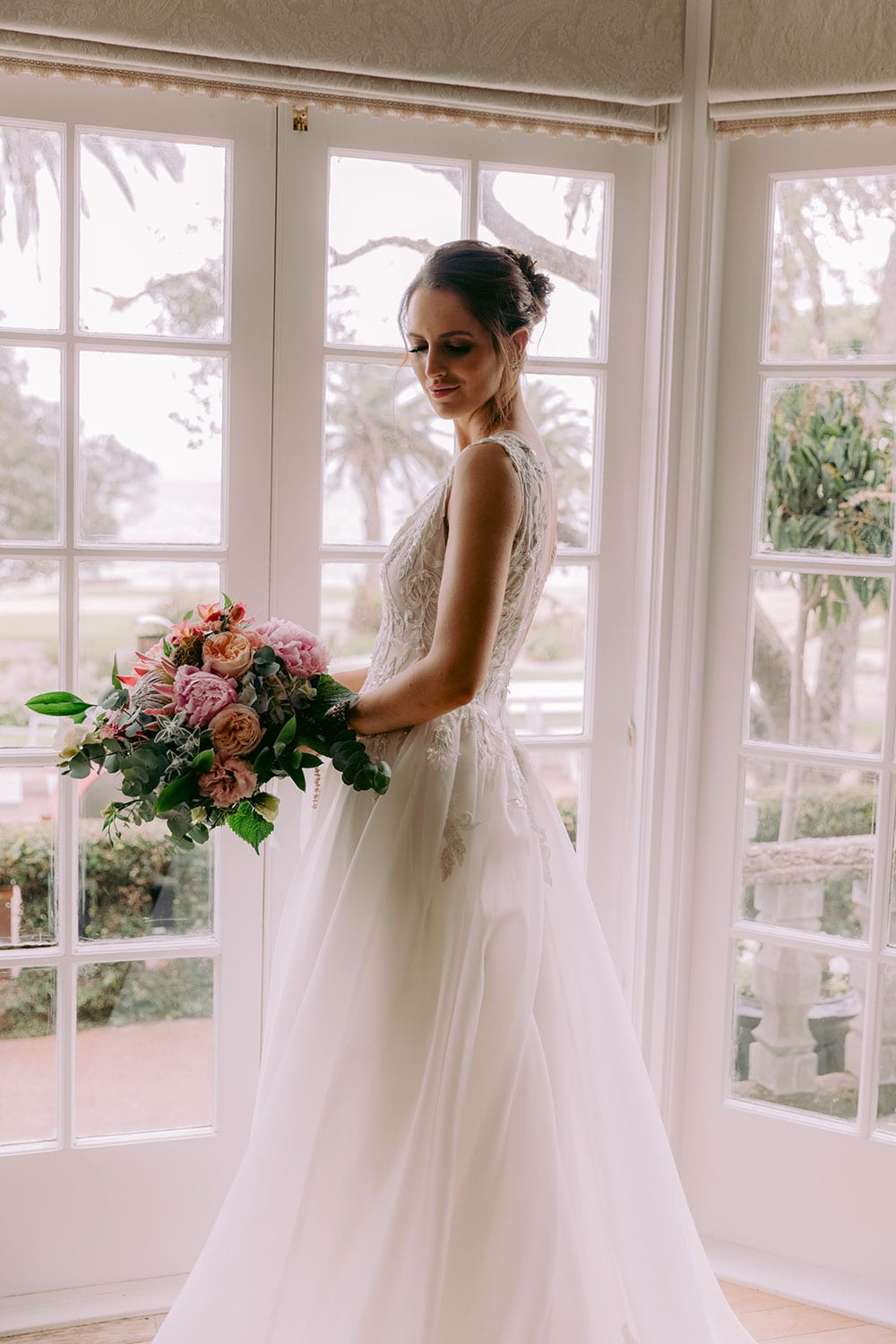 Rema Wedding gown from Vinka Design - This wedding dress has a bold design with a feminine style. Layers of dreamy satin organza with deep folds that open to reveal a split, and structured lace bodice that tapers at the waist to accentuates the figure. Model wearing gown holding bouquet in beautiful light conservatory.