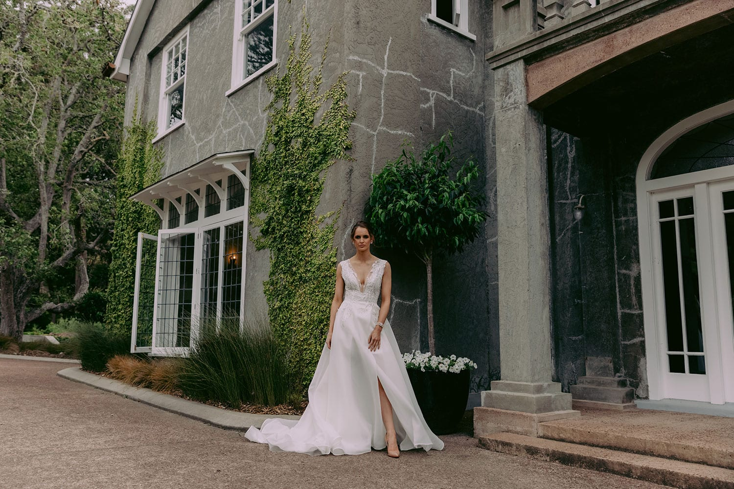 Rema Wedding gown from Vinka Design - This wedding dress has a bold design with a feminine style. Layers of dreamy satin organza with deep folds that open to reveal a split, and structured lace bodice that tapers at the waist to accentuates the figure. Model wearing gown outside old heritage building in Auckland..
