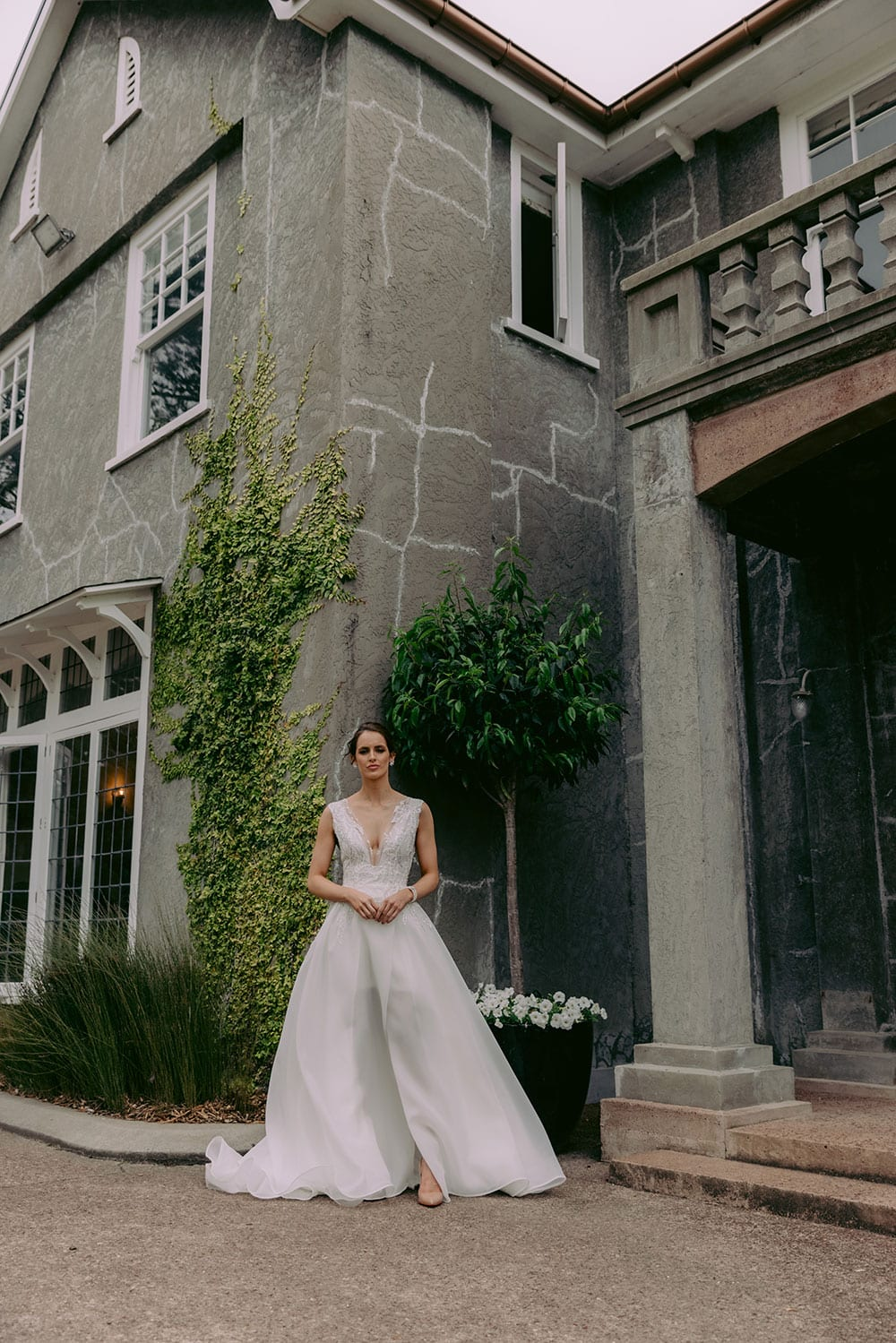 Rema Wedding gown from Vinka Design - This wedding dress has a bold design with a feminine style. Layers of dreamy satin organza with deep folds that open to reveal a split, and structured lace bodice that tapers at the waist to accentuates the figure. Model wearing gown showing full length of dress outside old heritage building in Auckland..