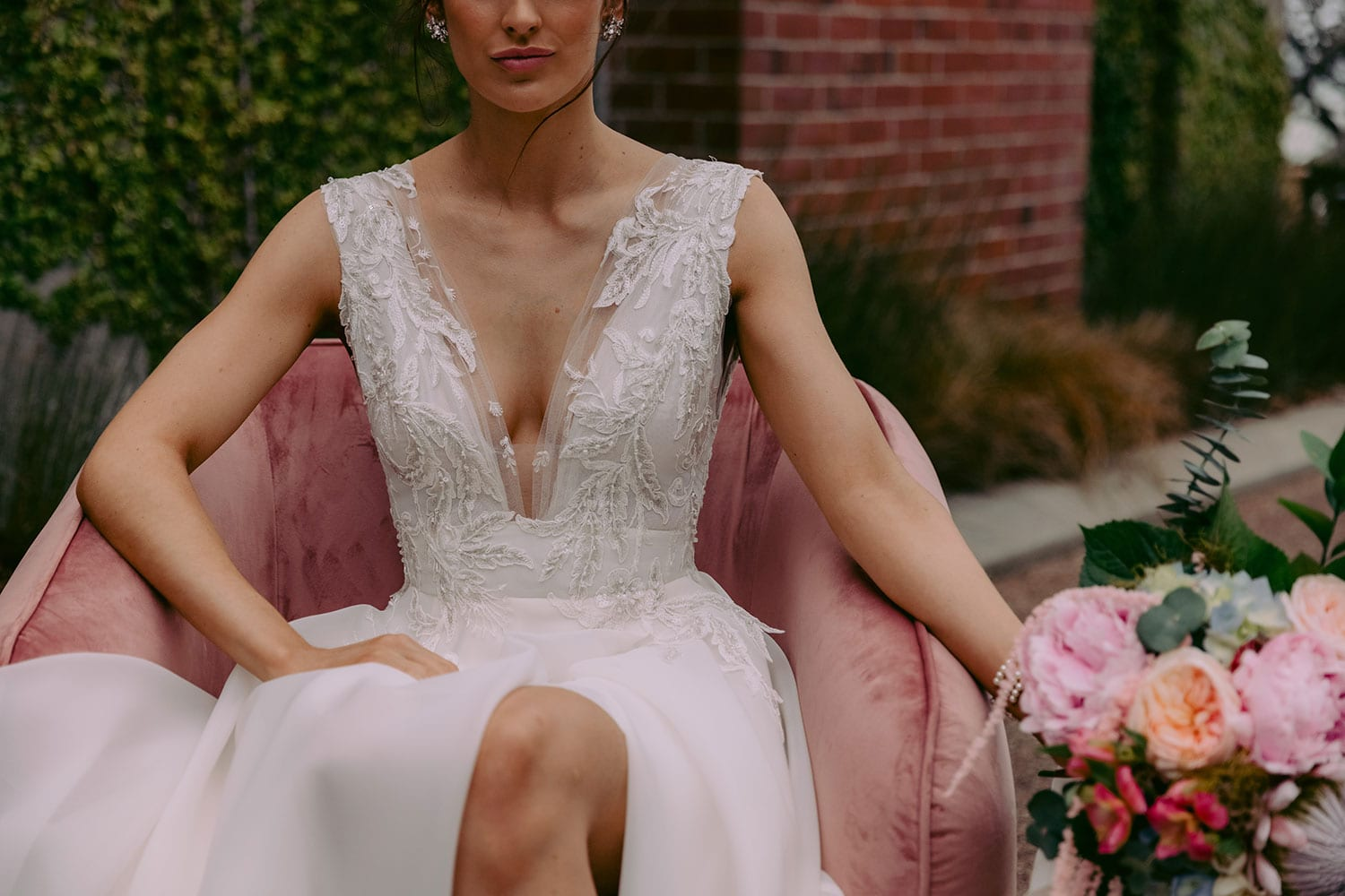 Rema Wedding gown from Vinka Design - This wedding dress has a bold design with a feminine style. Layers of dreamy satin organza with deep folds that open to reveal a split, and structured lace bodice that tapers at the waist to accentuates the figure. Model wearing gown seated on chair.