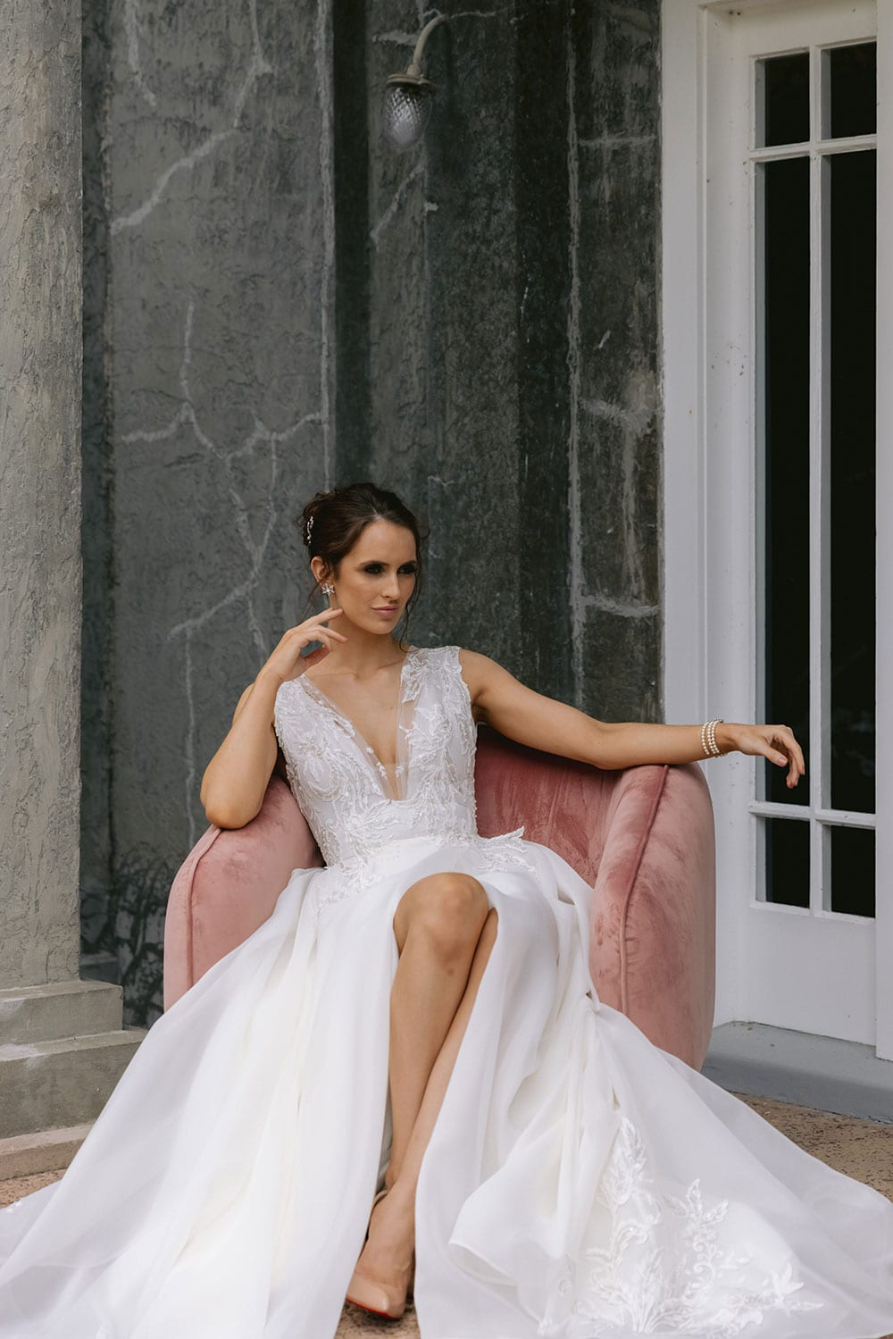 Rema Wedding gown from Vinka Design - This wedding dress has a bold design with a feminine style. Layers of dreamy satin organza with deep folds that open to reveal a split, and structured lace bodice that tapers at the waist to accentuates the figure. Model wearing gown seated with skirt layers and train flowing and split showing leg outside heritage building in Auckland..