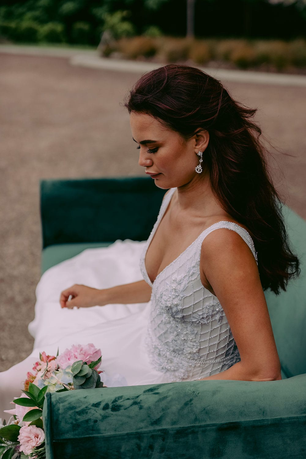 Reihana Wedding gown from Vinka Design - This stunning wedding dress features beautiful hand-appliqued beaded lace, a V-shaped neckline and low V-shaped back. The skirt is the epitome of elegance in dreamy silk chiffon, with an optional split. Model wearing gown while sitting on long sofa.