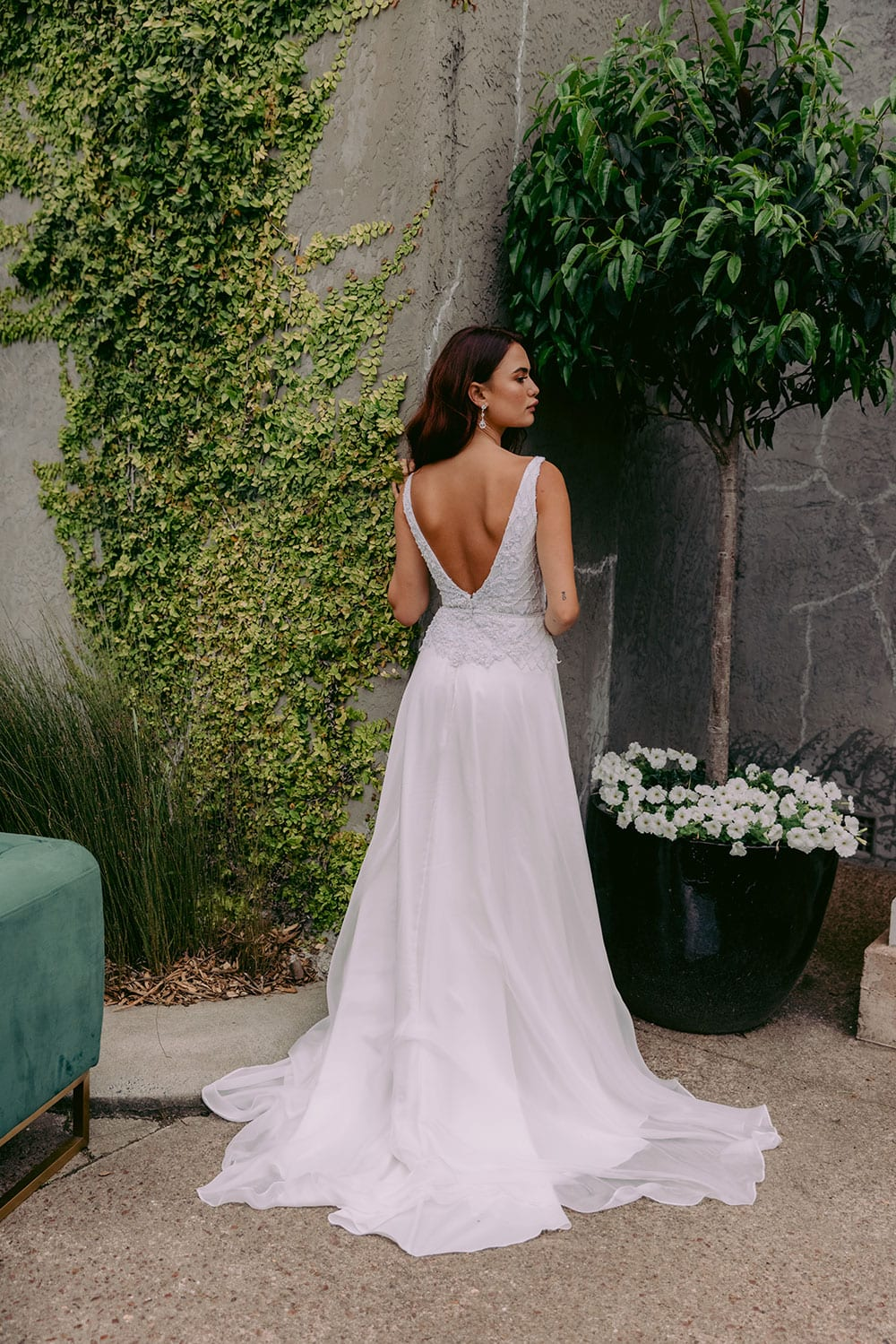 Reihana Wedding gown from Vinka Design - This stunning wedding dress features beautiful hand-appliqued beaded lace, a V-shaped neckline and low V-shaped back. The skirt is the epitome of elegance in dreamy silk chiffon, with an optional split. Model wearing gown showing full length of back, outside heritage building.