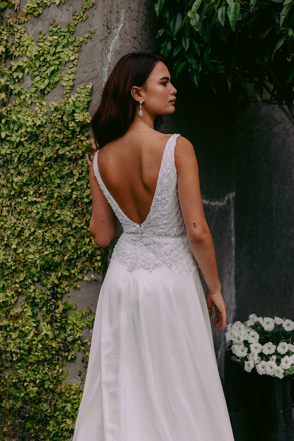 Reihana Wedding gown from Vinka Design - This stunning wedding dress features beautiful hand-appliqued beaded lace, a V-shaped neckline and low V-shaped back. The skirt is the epitome of elegance in dreamy silk chiffon, with an optional split. Model wearing gown showing close up of low V back of dress, outside heritage building.