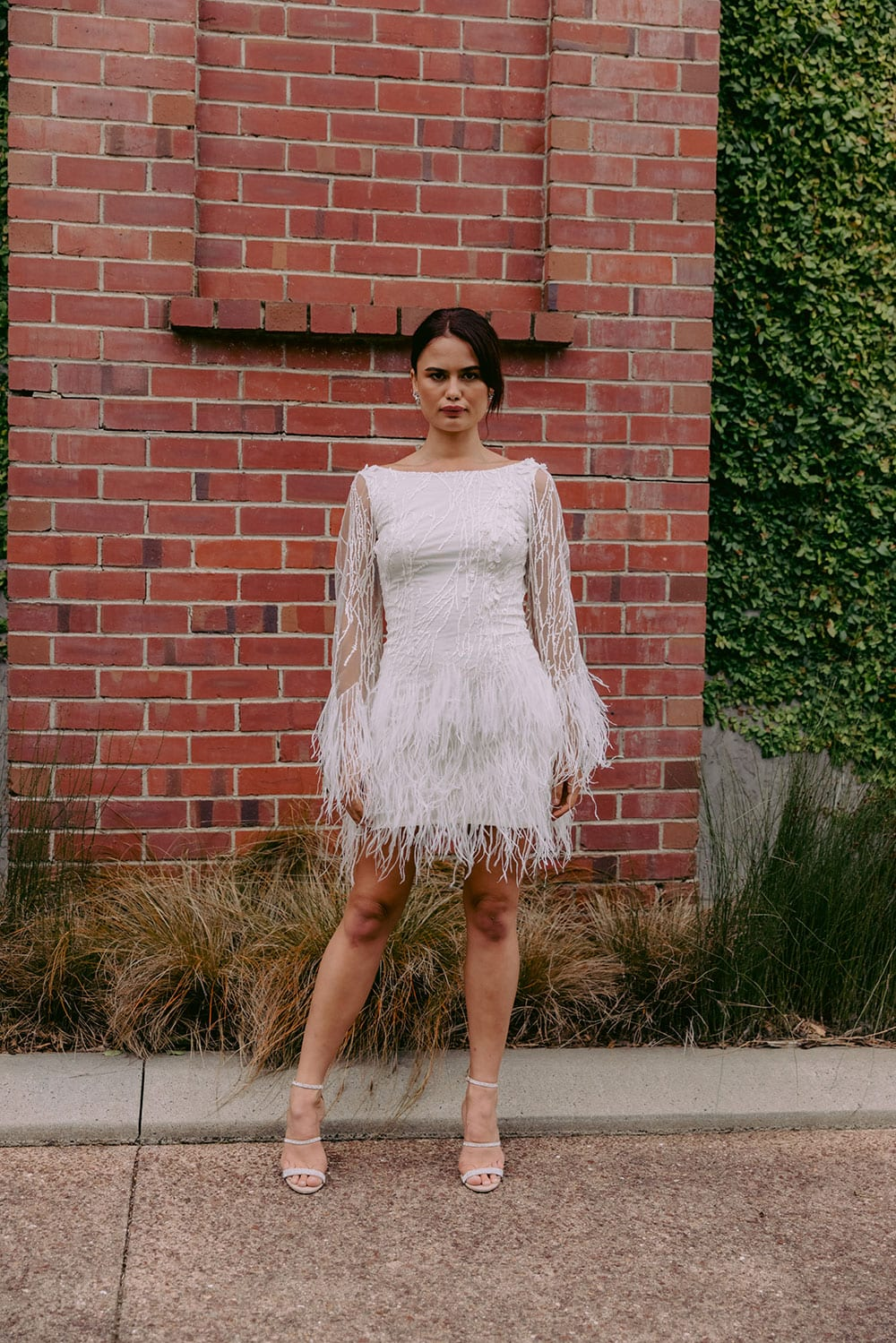 Nikora Wedding gown from Vinka Design - This sexy gown is sure to turn heads! Adorned with feathers that accentuate movement and bell sleeves that add flare, a high neckline, and low back. Model wearing gown against brick wall near Auckland.