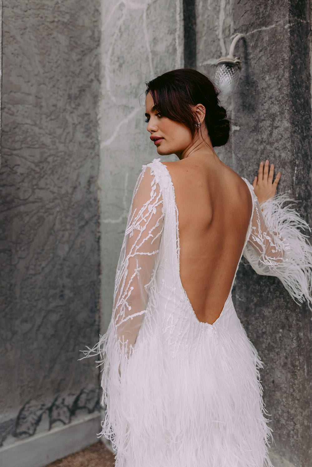 Nikora Wedding gown from Vinka Design - This sexy gown is sure to turn heads! Adorned with feathers that accentuate movement and bell sleeves that add flare, a high neckline, and low back. Model wearing gown facing away showing back of dress.