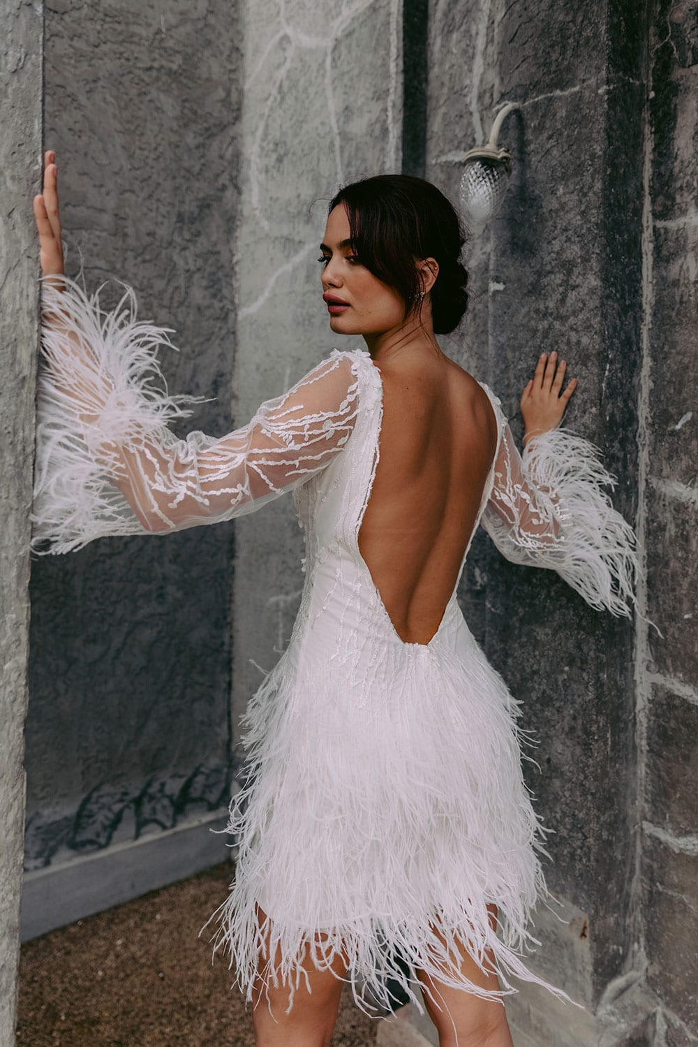 Nikora Wedding gown from Vinka Design - This sexy gown is sure to turn heads! Adorned with feathers that accentuate movement and bell sleeves that add flare, a high neckline, and low back. Model wearing gown facing away with arms raised showing back of dress and long sleeves.