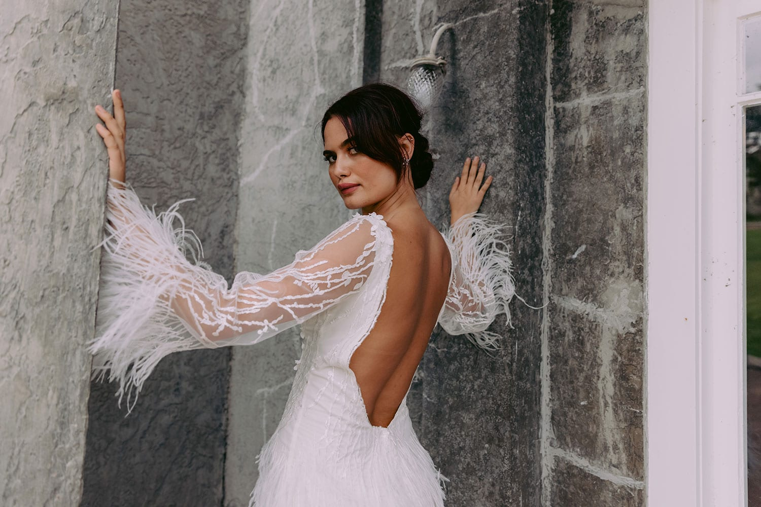 Nikora Wedding gown from Vinka Design - This sexy gown is sure to turn heads! Adorned with feathers that accentuate movement and bell sleeves that add flare, a high neckline, and low back. Model wearing gown facing away with arms raised showing back of dress and sleeves.