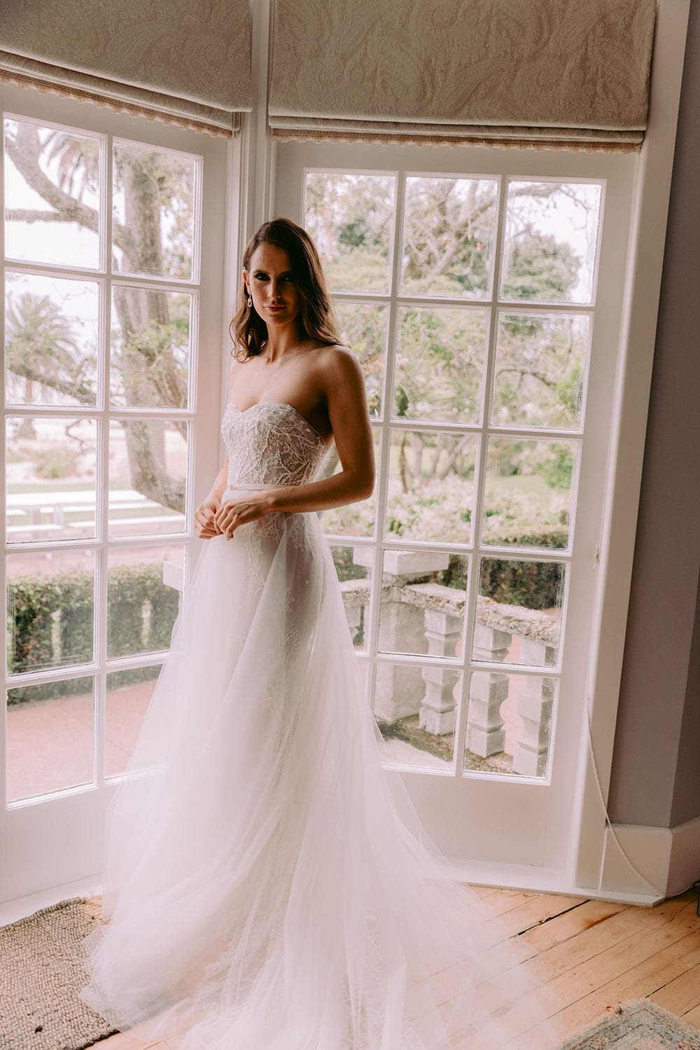 Nera Wedding gown from Vinka Design - Feminine, form-fitting strapless lace wedding dress. Boned stretch base that sculpts and hugs the figure with delicate blossom lace appliqued by hand in to flatter the shape of the body. Model wearing gown in beautifully lit windows of feature room.