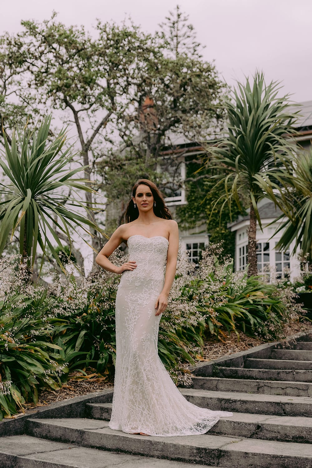 Nera Wedding gown from Vinka Design - Feminine, form-fitting strapless lace wedding dress. Boned stretch base that sculpts and hugs the figure with delicate blossom lace appliqued by hand in to flatter the shape of the body. Model wearing gown in Clevedon Gardens near Auckland.
