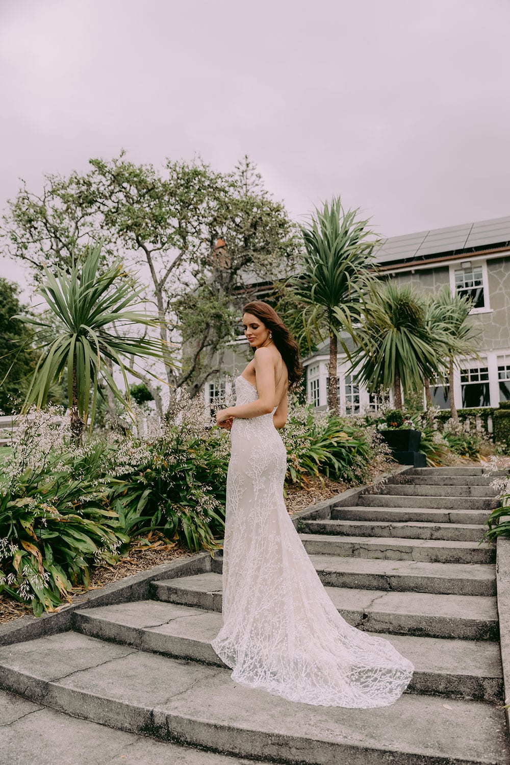Nera Wedding gown from Vinka Design - Feminine, form-fitting strapless lace wedding dress. Boned stretch base that sculpts and hugs the figure with delicate blossom lace appliqued by hand in to flatter the shape of the body. Model wearing gown showing full length dress in Clevedon Gardens near Auckland.