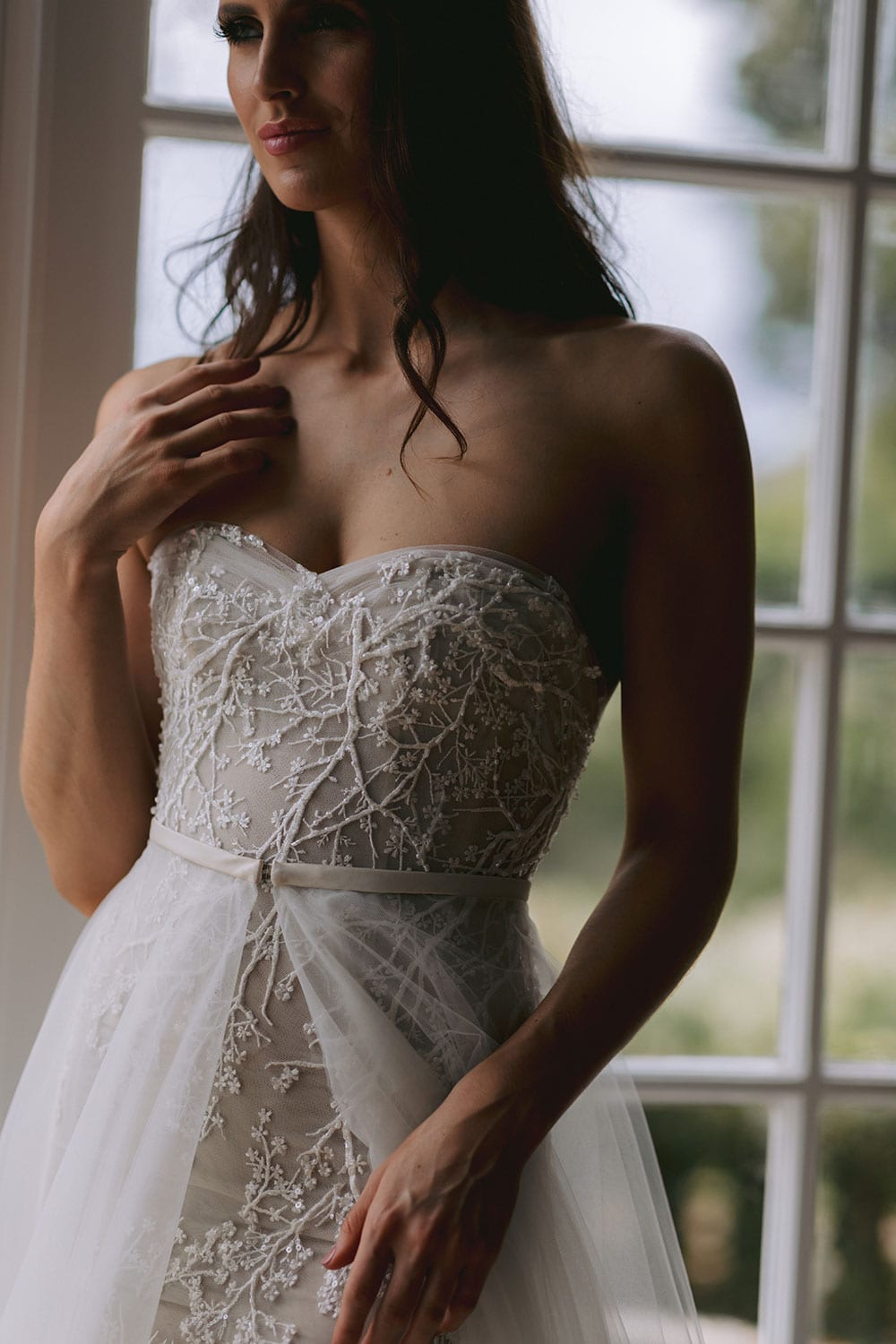 Nera Wedding gown from Vinka Design - Feminine, form-fitting strapless lace wedding dress. Boned stretch base that sculpts and hugs the figure with delicate blossom lace appliqued by hand in to flatter the shape of the body. Model wearing gown showing intricate hand appliqued lace detail.
