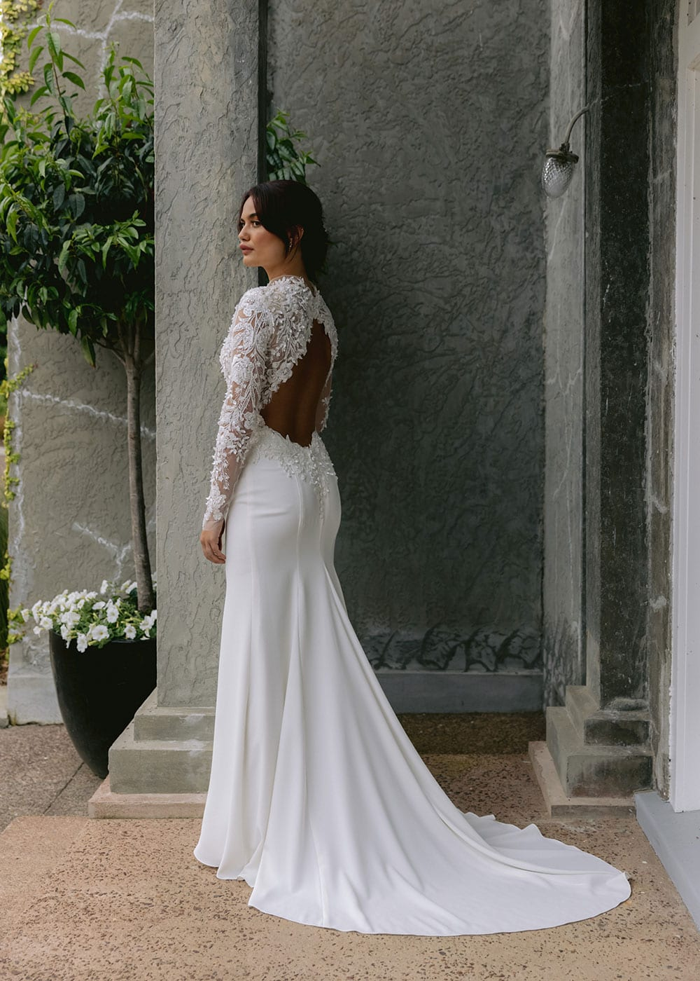 Moana Wedding gown from Vinka Design - Spectacular wedding dress perfect for the modern bride who still wants a classic spark! 3D lace embroidery complemented by a high neckline, fitted sleeves, and stunning low back into a flare train. Model wearing gown showing full length with train behind.