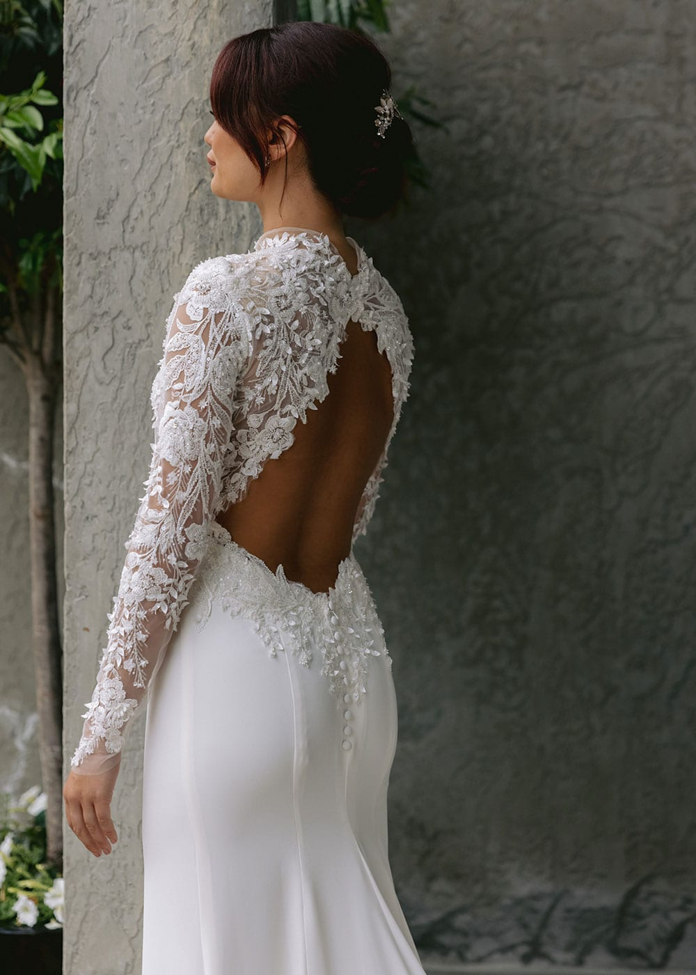 Moana Wedding gown from Vinka Design - Spectacular wedding dress perfect for the modern bride who still wants a classic spark! 3D lace embroidery complemented by a high neckline, fitted sleeves, and stunning low back into a flare train. Model wearing gown showing low back and lace detail.