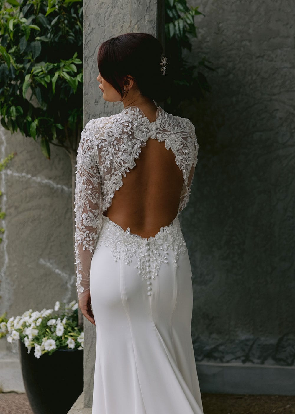 Moana Wedding gown from Vinka Design - Spectacular wedding dress perfect for the modern bride who still wants a classic spark! 3D lace embroidery complemented by a high neckline, fitted sleeves, and stunning low back into a flare train. Model wearing gown showing open back and lace detail.