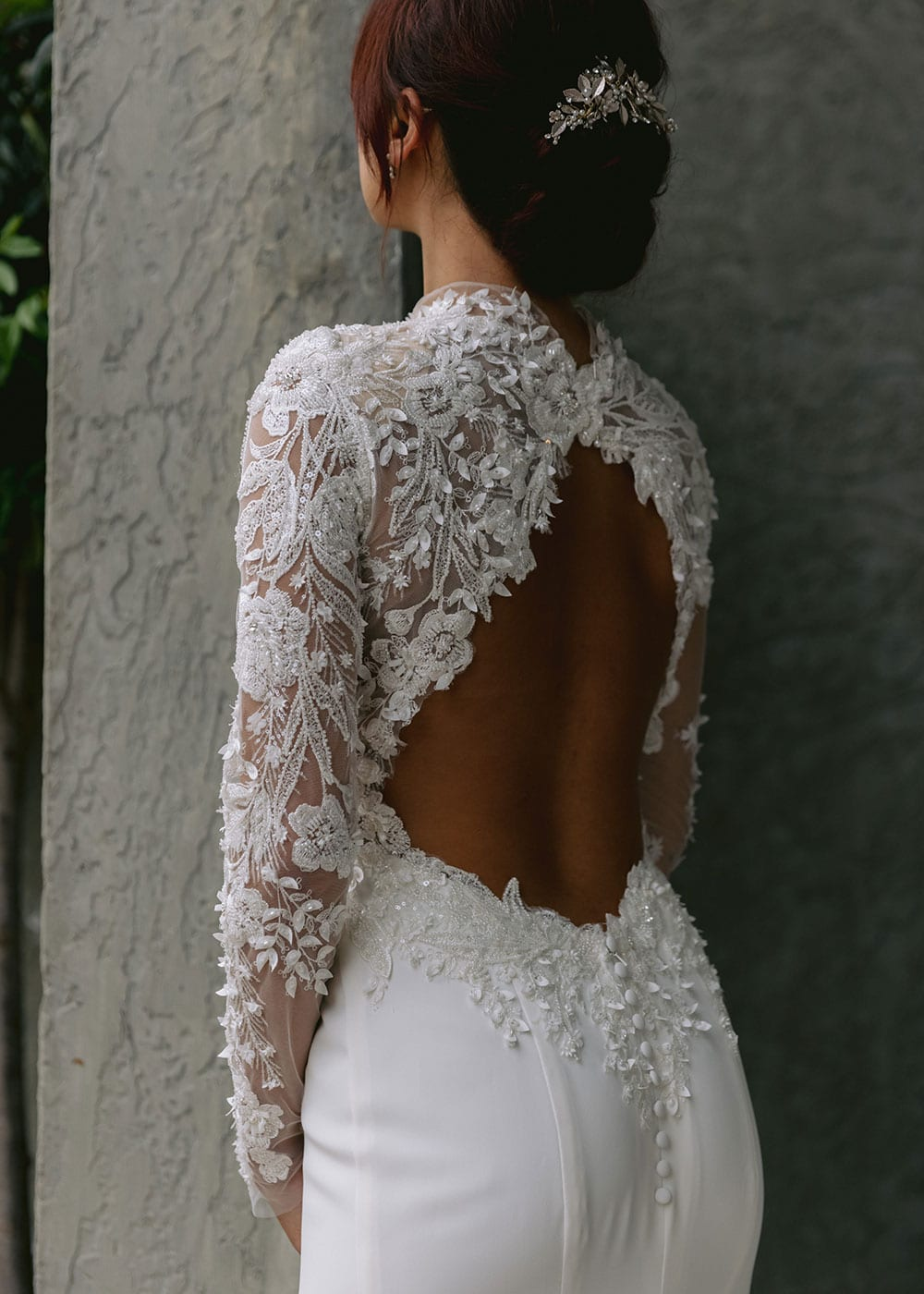 Moana Wedding gown from Vinka Design - Spectacular wedding dress perfect for the modern bride who still wants a classic spark! 3D lace embroidery complemented by a high neckline, fitted sleeves, and stunning low back into a flare train. Model wearing gown showing open back and 3D lace detail.