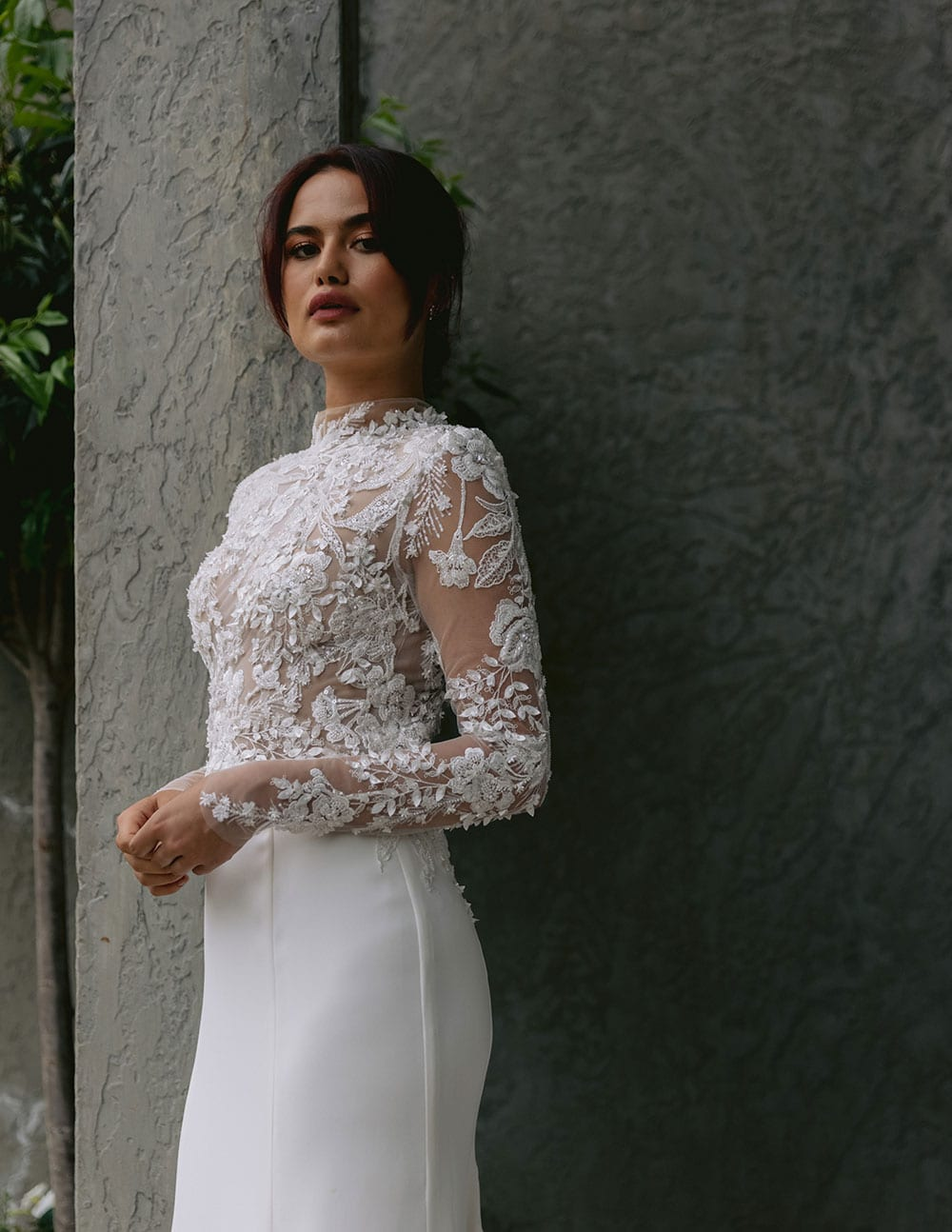 Moana Wedding gown from Vinka Design - Spectacular wedding dress perfect for the modern bride who still wants a classic spark! 3D lace embroidery complemented by a high neckline, fitted sleeves, and stunning low back into a flare train. Model wearing gown showing 3D lace detail at front.
