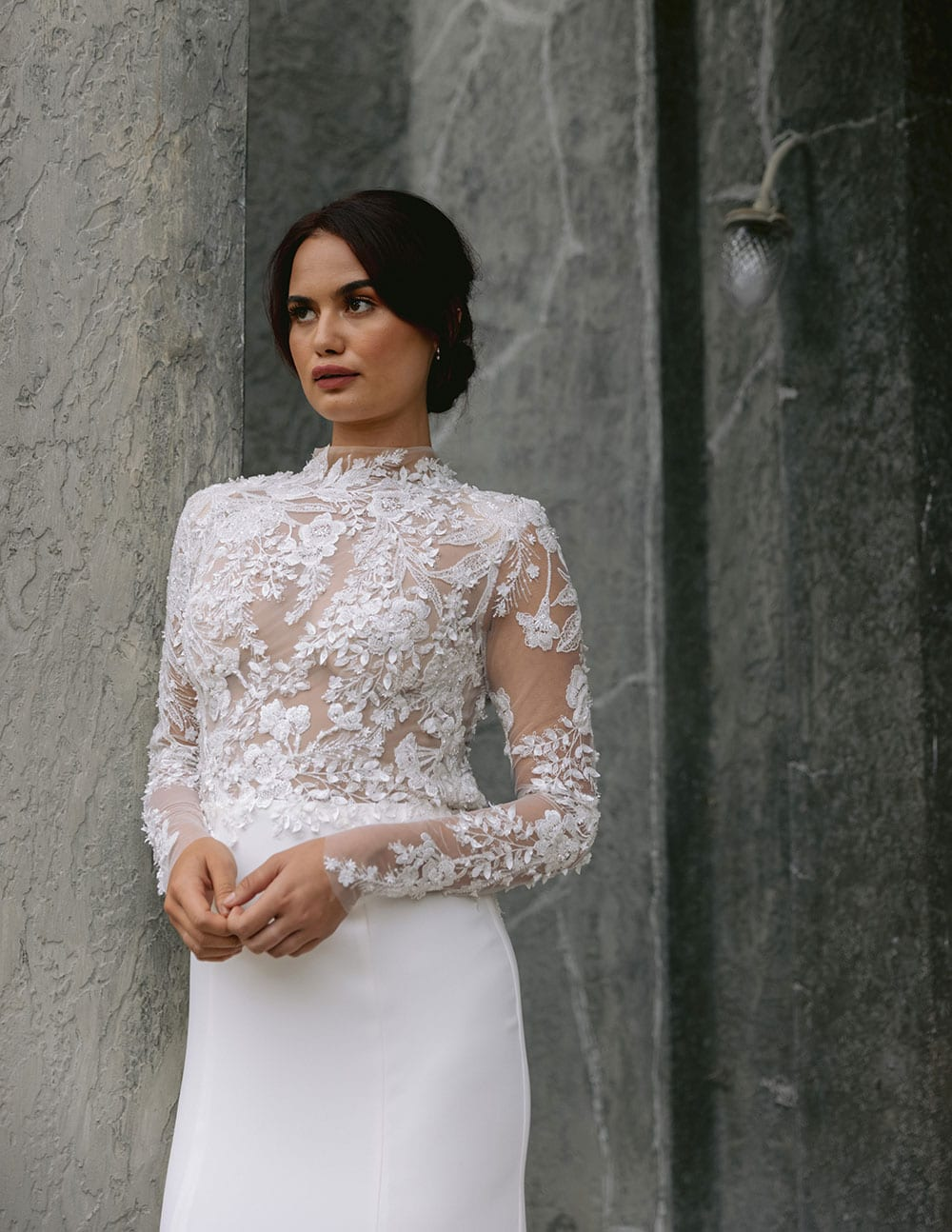 Moana Wedding gown from Vinka Design - Spectacular wedding dress perfect for the modern bride who still wants a classic spark! 3D lace embroidery complemented by a high neckline, fitted sleeves, and stunning low back into a flare train. Model wearing gown showing 3D lace detail at front and long sleeves.