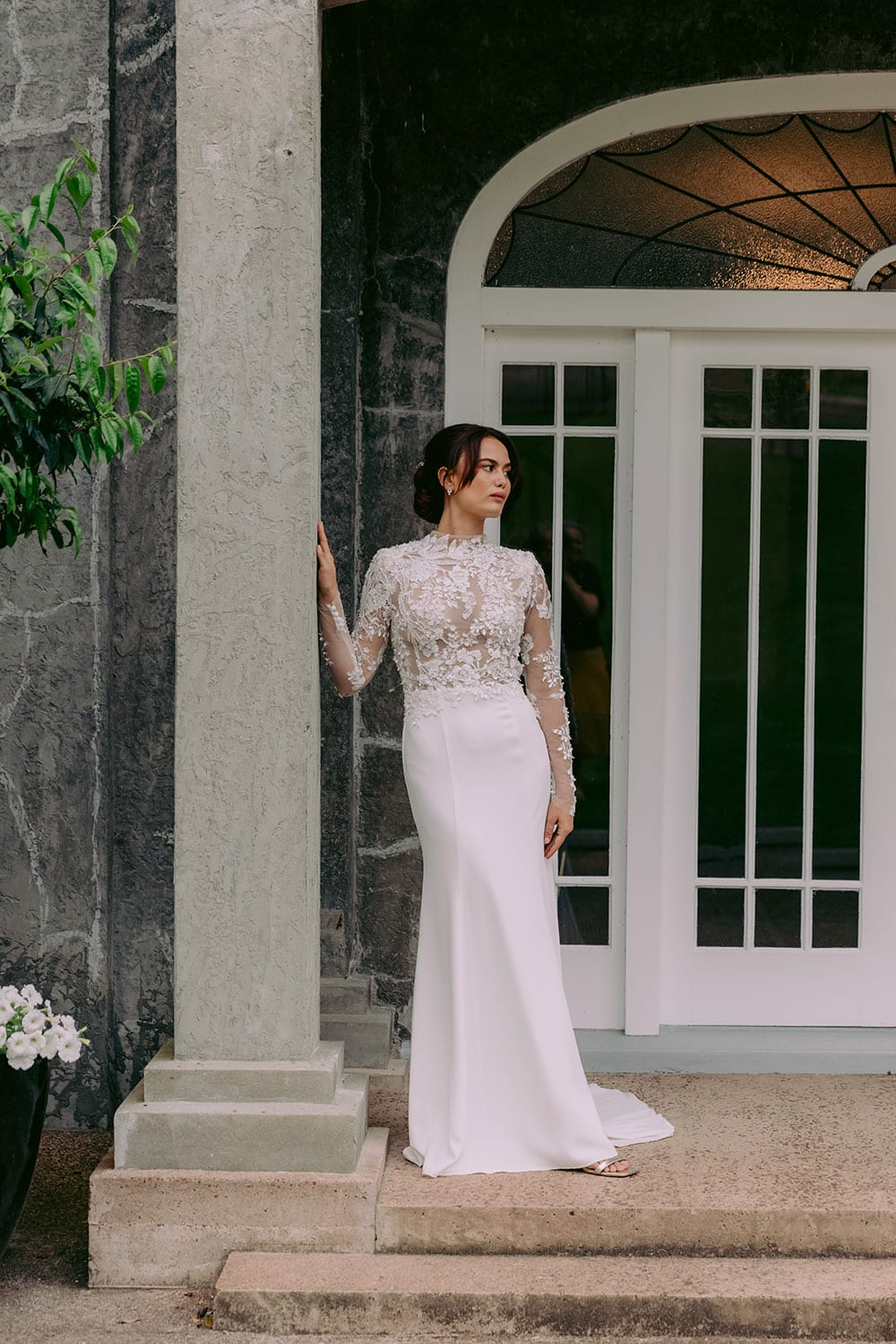 Moana Wedding gown from Vinka Design - Spectacular wedding dress perfect for the modern bride who still wants a classic spark! 3D lace embroidery complemented by a high neckline, fitted sleeves, and stunning low back into a flare train. Model wearing gown showing full length of dress.