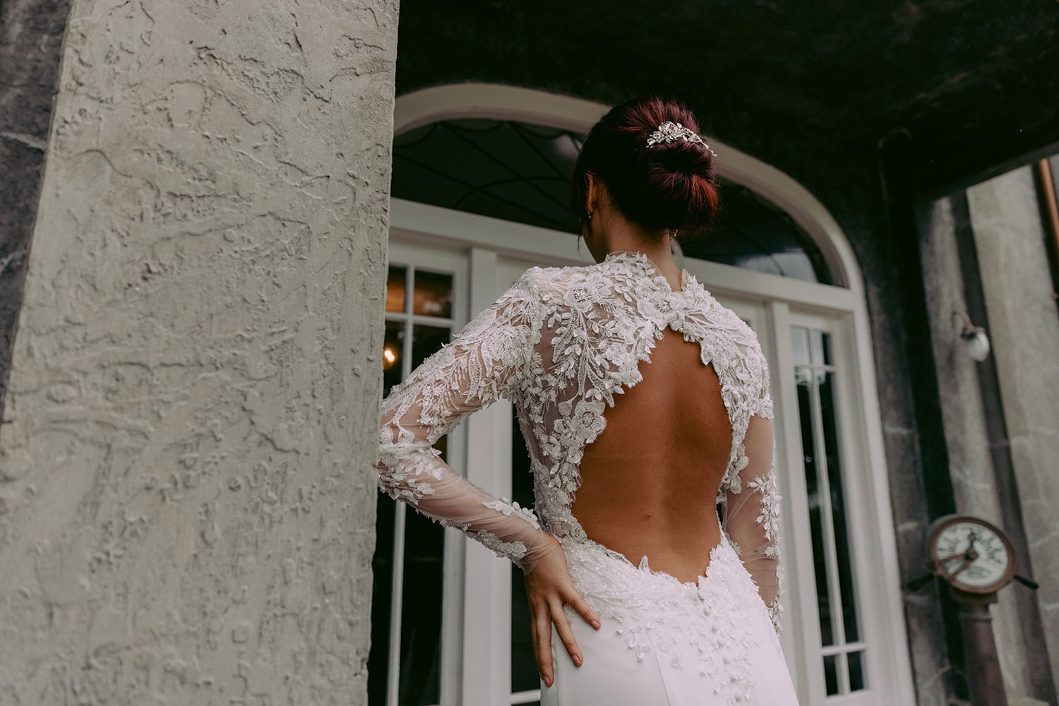 Moana Wedding gown from Vinka Design - Spectacular wedding dress perfect for the modern bride who still wants a classic spark! 3D lace embroidery complemented by a high neckline, fitted sleeves, and stunning low back into a flare train. Model wearing gown hand on hip showing top half of dress from the back.